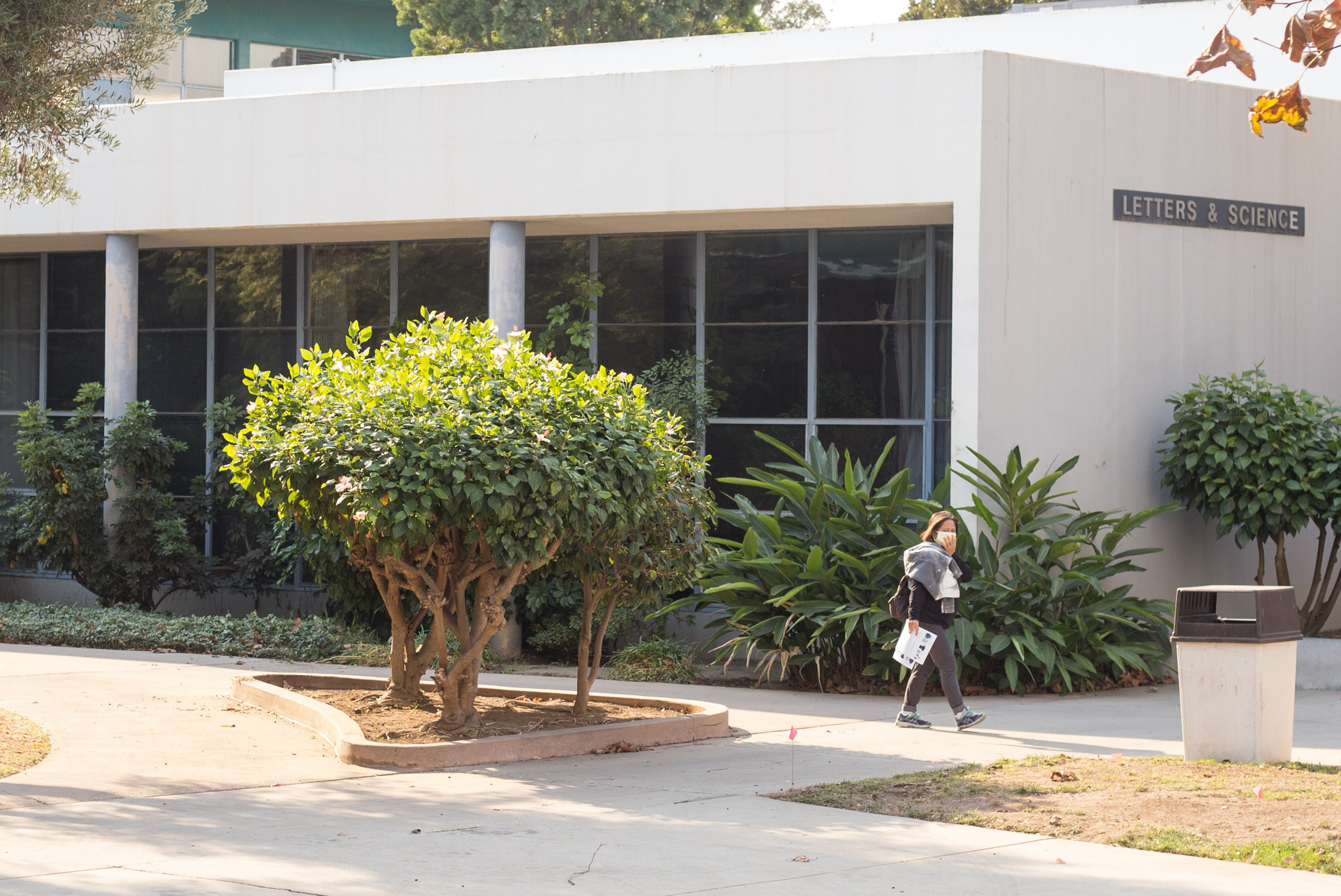 """A Santa Monica Student walks by the Letters & Science building on SMC's main campus. She is wearing a mask because of the poor air quality from the Skirball fire. An email was sent to all students at 8:49 am informing students that classes are canceled due to the close proximity to the Skirball fire on Wednesday, December 6th 2017 in Santa Monica, Calif. The email stated that the """"fire is affecting the air quality and the road conditions in and around SMC area"""". (Photo by: Thane Fernandes)"""