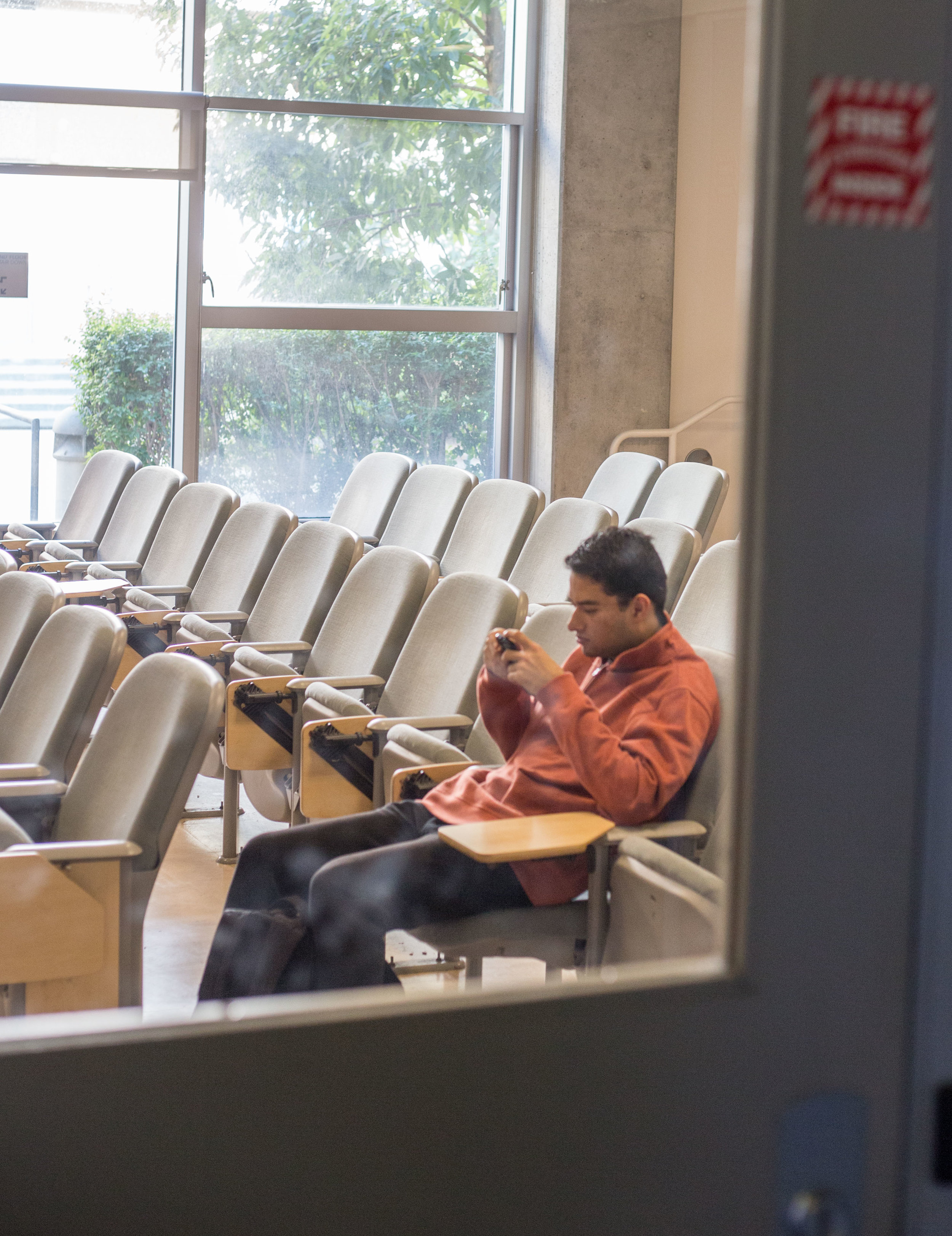 """Santa Monica College student, refused to give name, sits alone in a classroom after SMC students were notified via email and phone call that all classes on Wednesday, December 6th were canceled due to the close proximity to the Skirball fire. This took place on SMC's Main Campus Humanities and Social Sciences building on Wednesday, December 6th 2017 in Santa Monica, Calif. The email stated that the """"fire is affecting the air quality and the road conditions in and around SMC area"""" and was sent out at 8:49 am. (Photo by: Thane Fernandes)"""