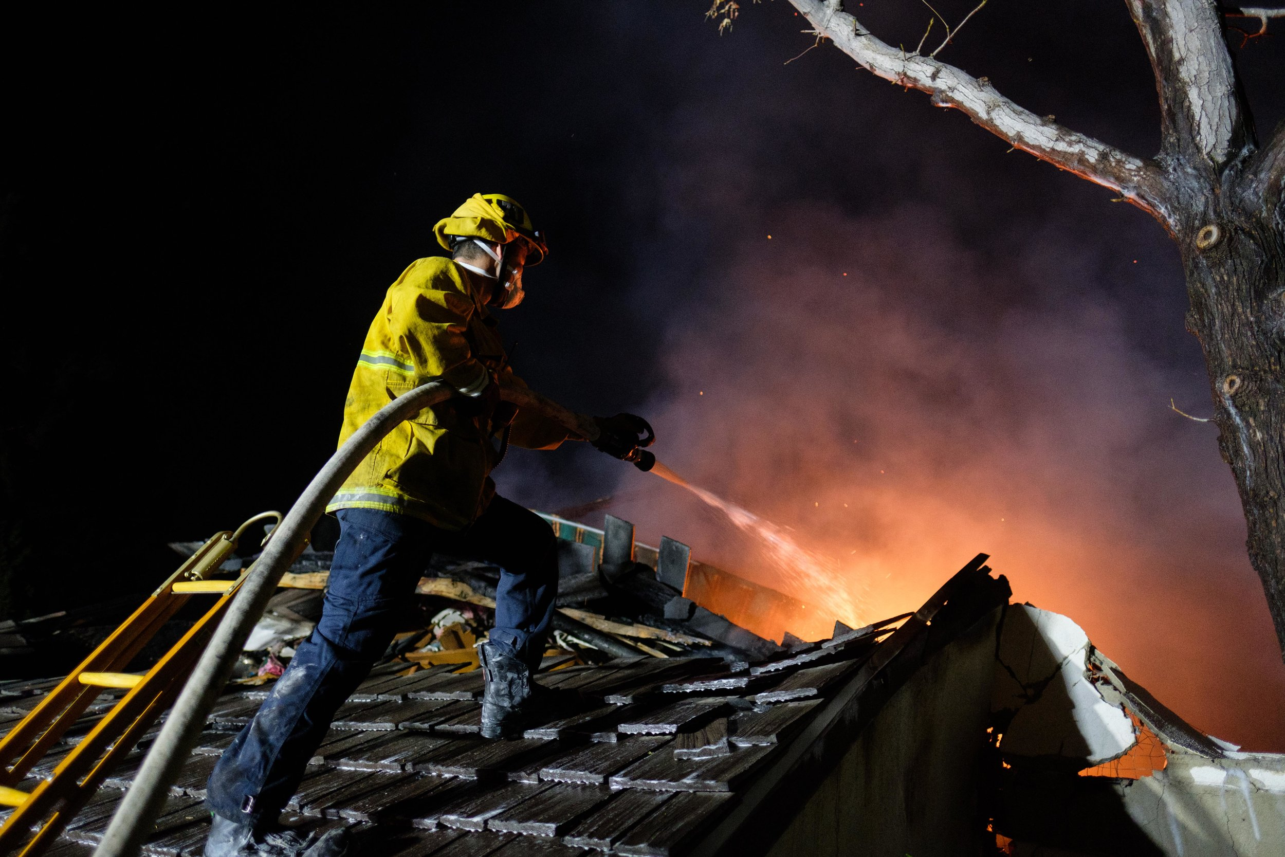 Los Angeles Fire Department firefighter on a rooftop, hosing down a flame inside the house. The LAFD has been battling the Skirball Fire since the early morning of Dec. 6, 2017. In Los Angeles, Calif. (Photo by Jayrol San Jose)