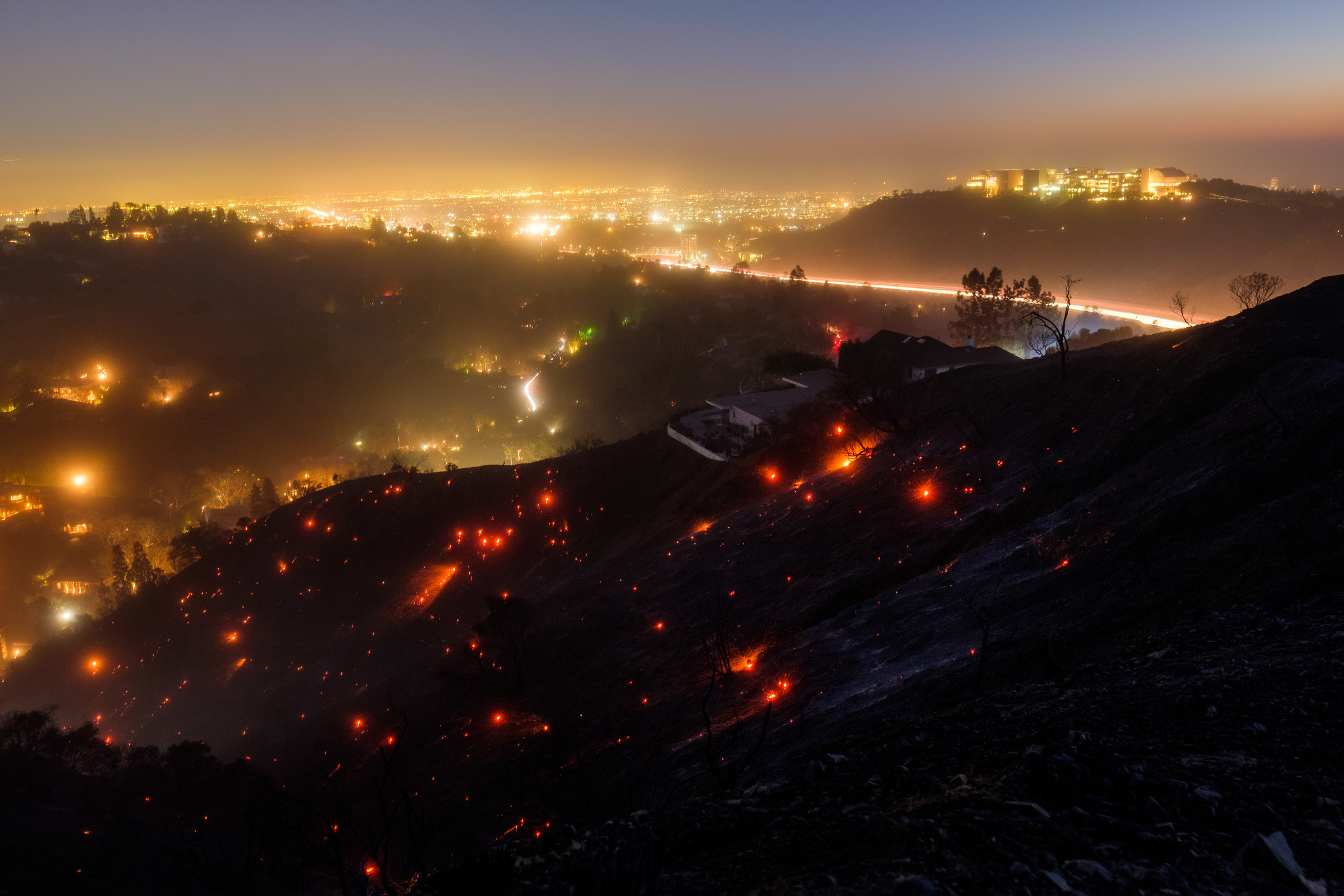 After sundown, the winds start to pick up on the Getty View Trail and embers from the Skirball Fire that burned down 475 acres of land at Sepulveda Pass. The fire started in the early morning and began to glow again in Santa Monica, Calif. On Dec. 6, 2017. (Photo by Jayrol San Jose)