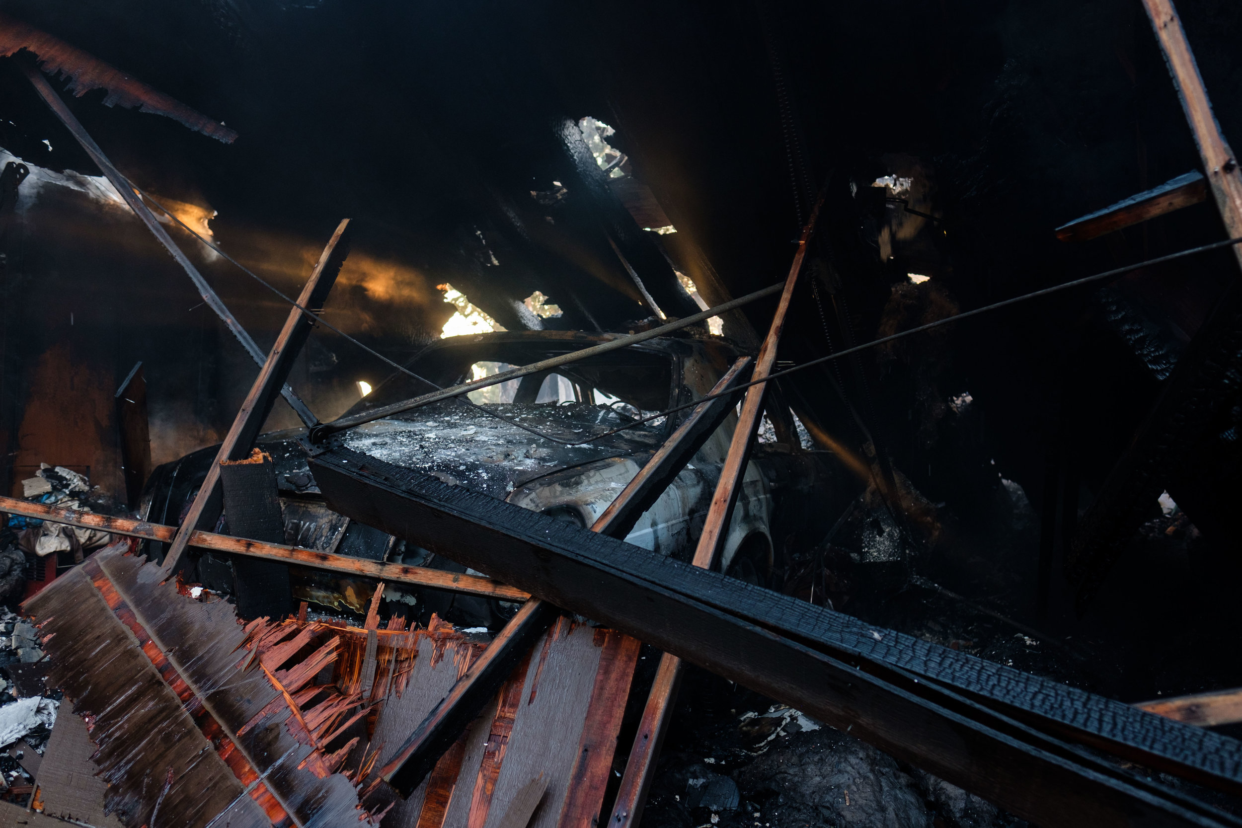 A garage collapsed on top of a Bentley, caused by the Skirball Fire in Los Angeles, Calif. On Dec. 6, 2017. (Photo by Jayrol San Jose)