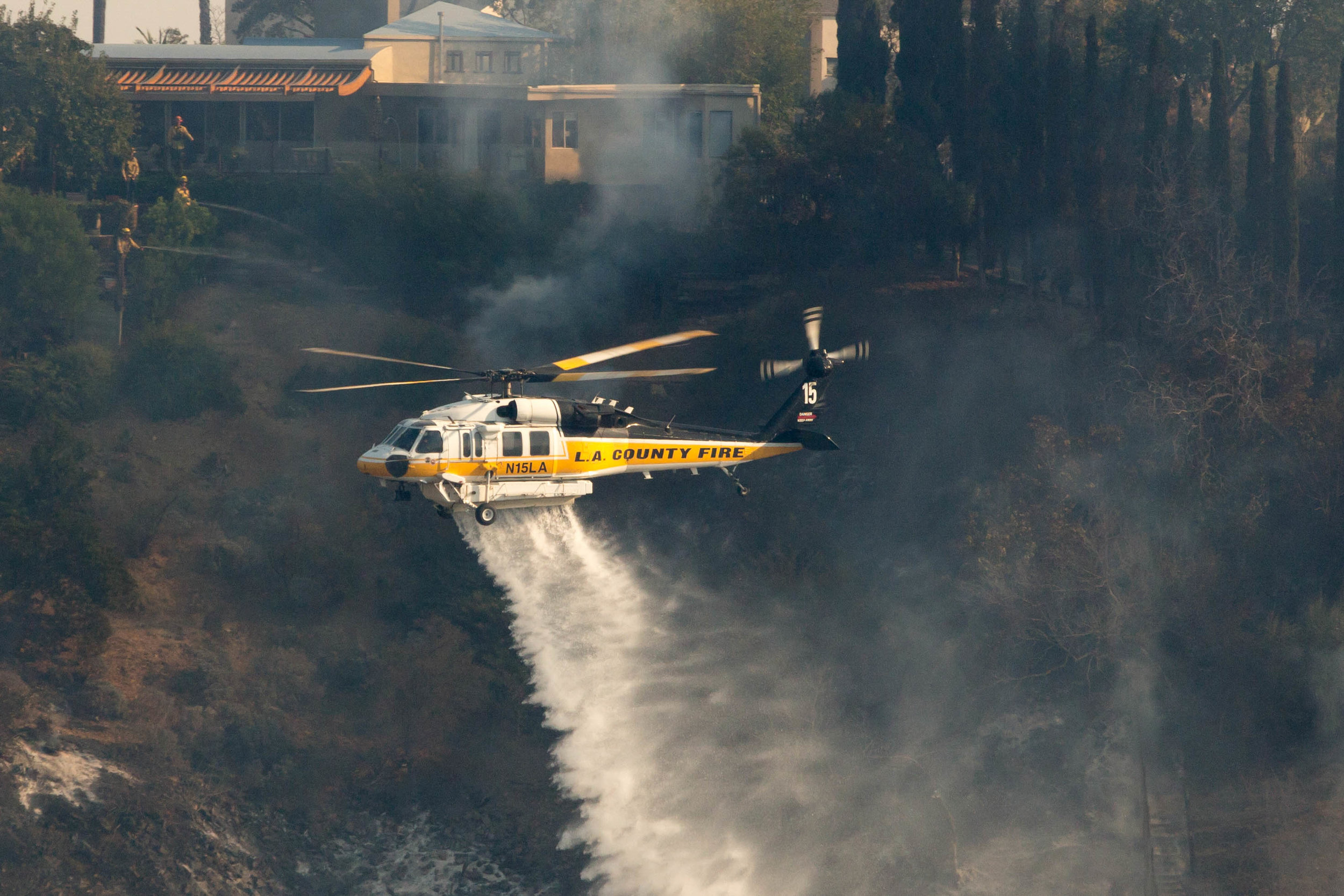 A Los Angeles County Fire helicopter makes a water drop on a vineyard during the Skirball Fire as firefighters on the ground work to keep the fire away on Wednesday, Dec.6, 2017 in the Bel-Air area of Los Angeles, Calif. (Jose Lopez)