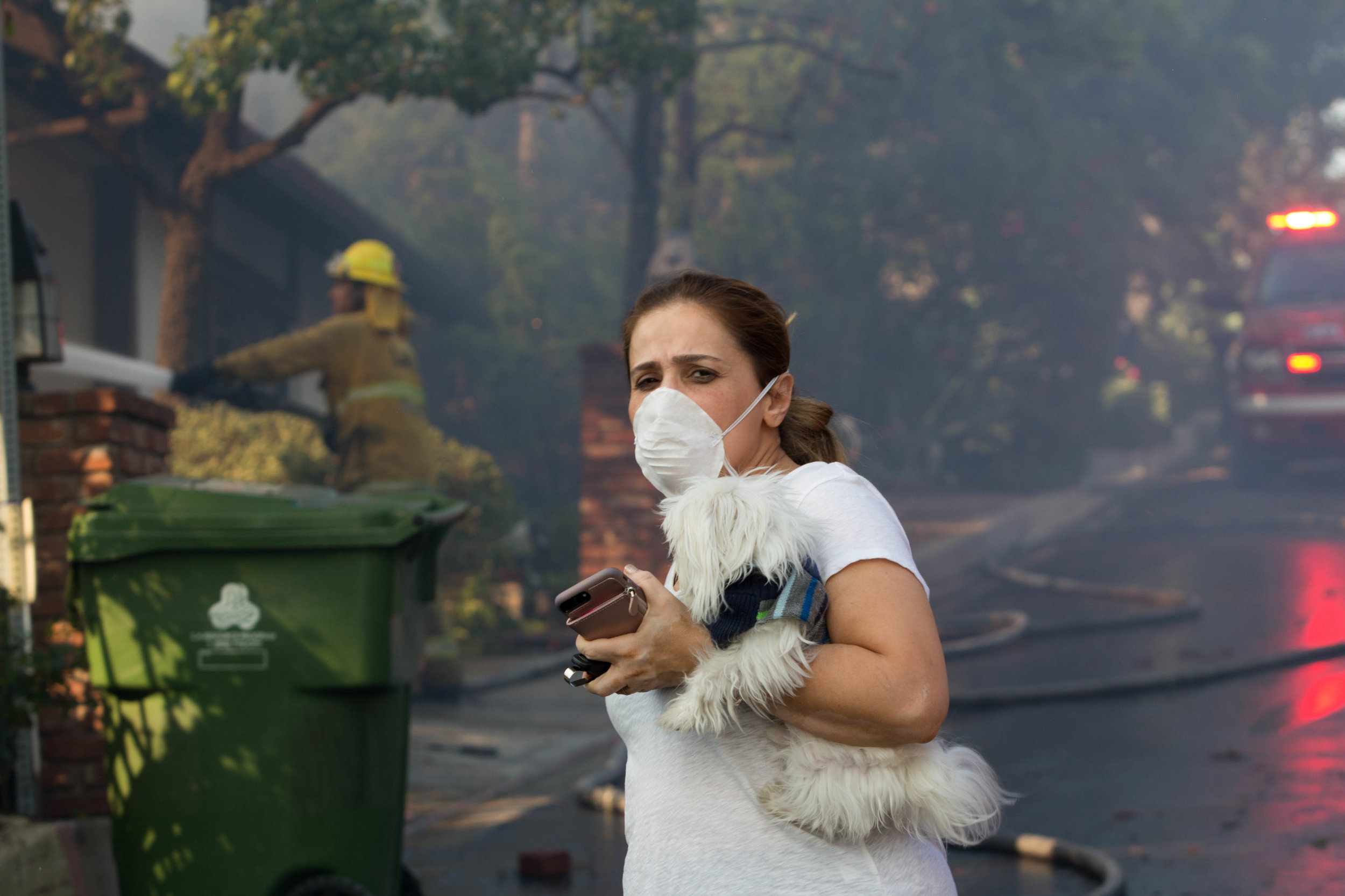 A distraught resident evacuates from her home along Casiano Road with her pet during the Skirball Fire on Wednesday, Dec.6, 2017 in Los Angeles, California. (Jose Lopez)