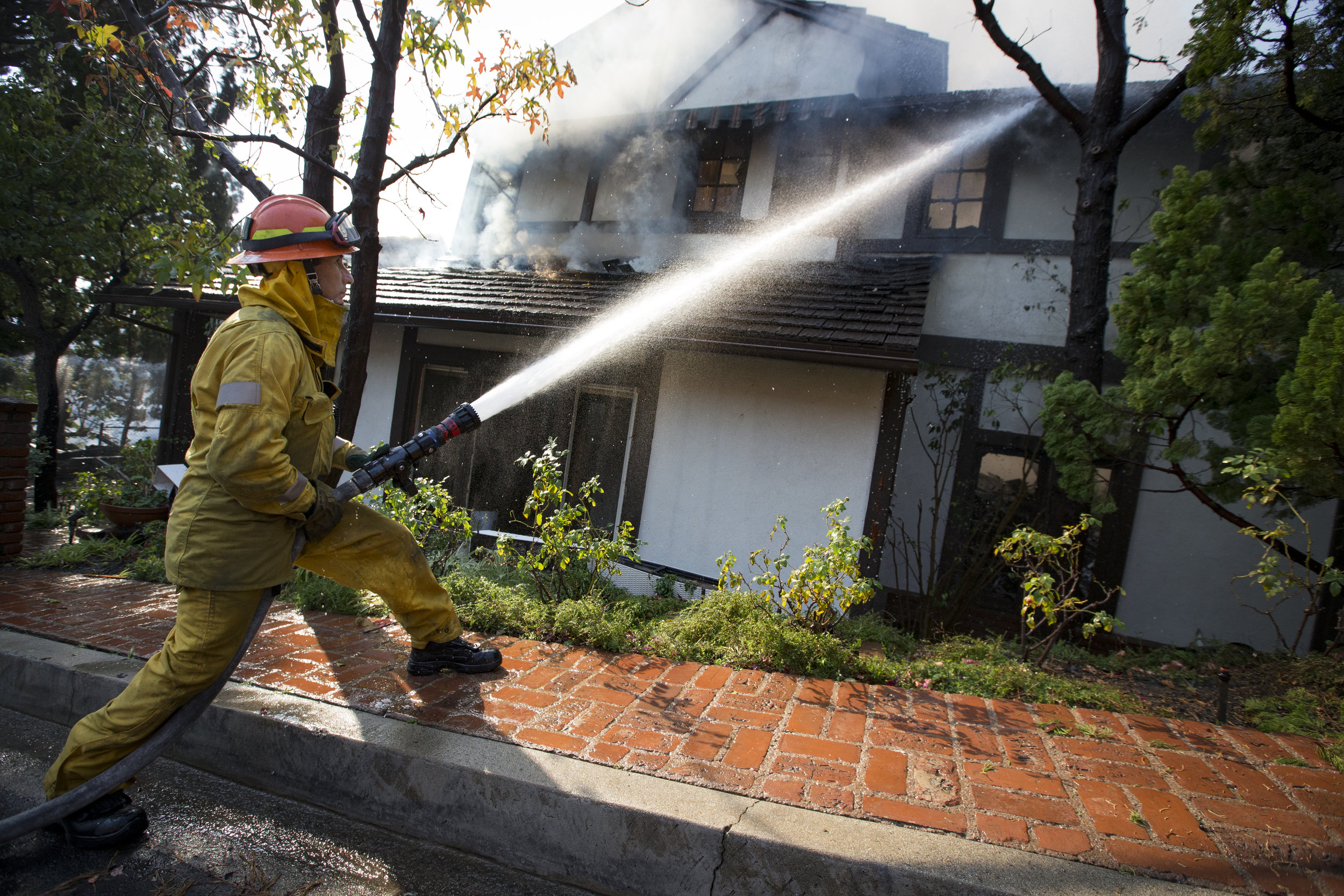 Los Angeles Fire Department engine company 71 firefighter David Valadez readies a hose to put out the flames of a burning house at The Skirball Fire which shut down the 405 north and burned 450 acres of land on Dec.6, 2017 in west Los Angeles, Calif. (Photo by Daniel Bowyer)