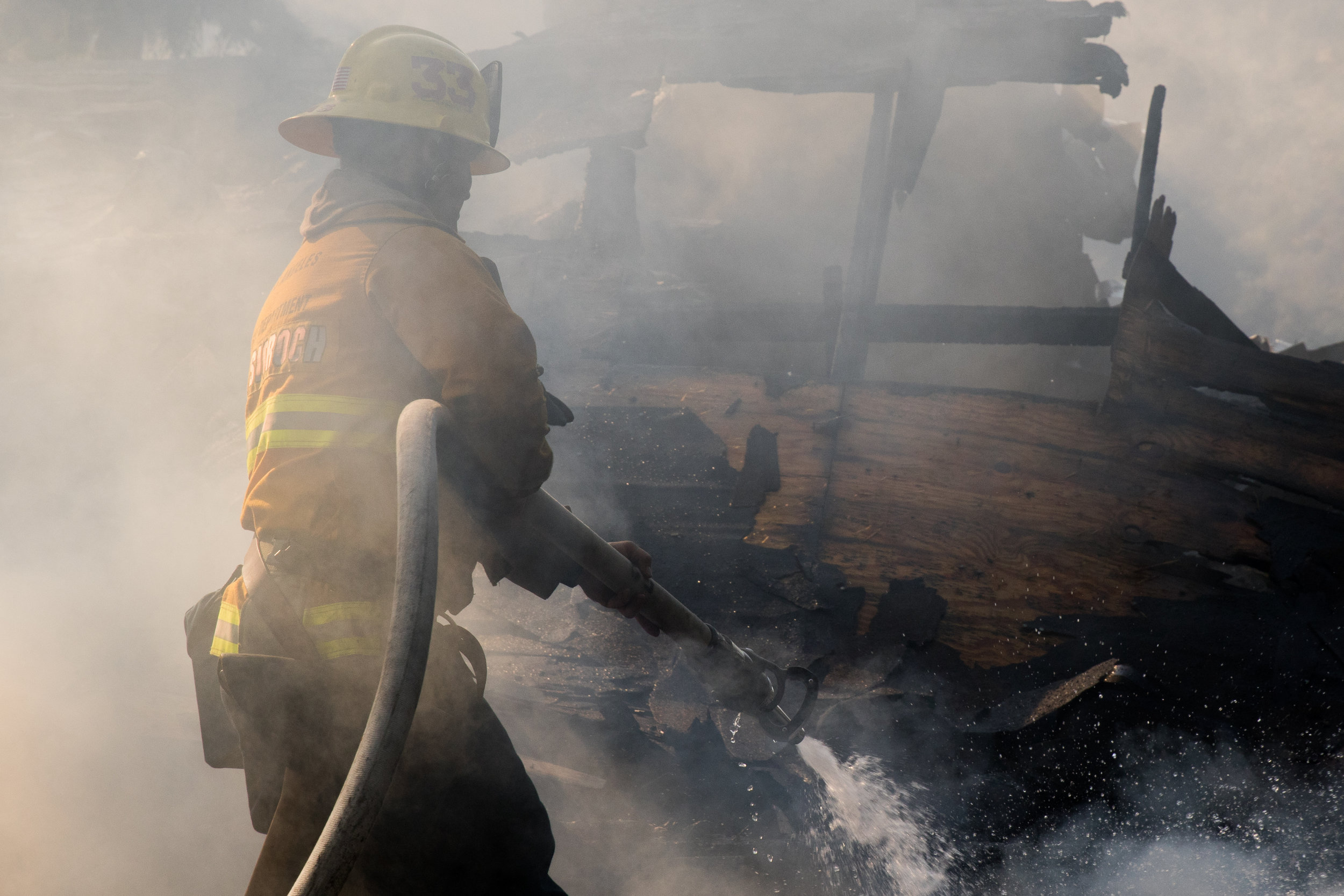 Scott Kwasigroch prepares his hose to battle one of the many house fires that occurred because of the Skirball Fire. The fire burned 450 acres and shut down the 405 freeway on Dec.6, 2017 in West Los Angeles Calif. (Photo by Zane Meyer-Thornton)