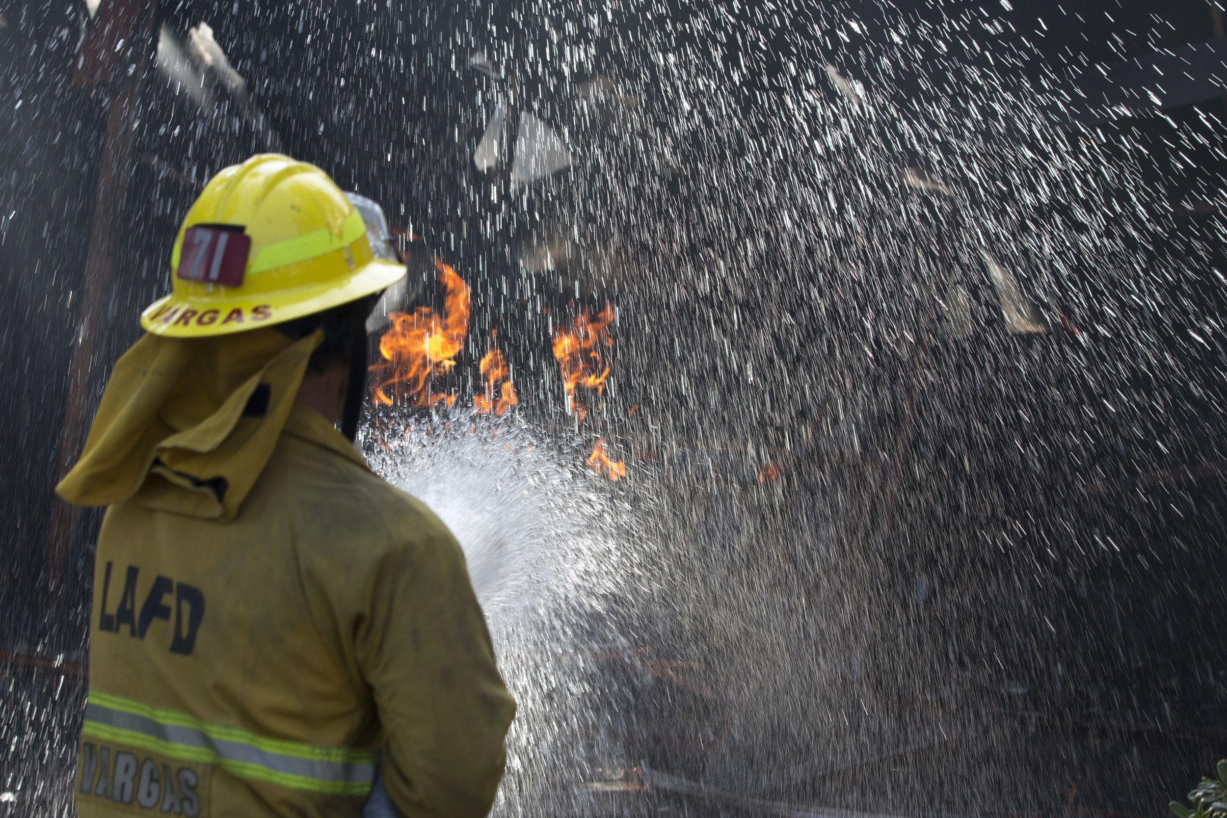 Los Angeles City firefighter Luis Vargas, from Engine 71, sprays down a car on fire inside a garage on Casiano Road during the Skirball fire on Wednesday, Dec.6, 2017 in the Bel-Air area of Los Angeles, Calif. (Jose Lopez)