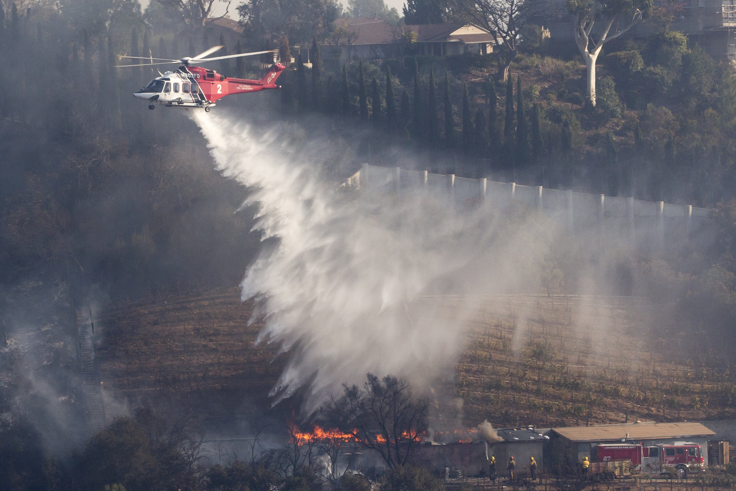 A Los Angeles County Fire helicopter makes a water drop on the Moraga Bel Air Vineyard,during the Skirball Fire as firefighters on the ground work to keep the fire away. On Wednesday, Dec.6, 2017 in the Bel-Air area of Los Angeles, Calif. (Jose Lopez)