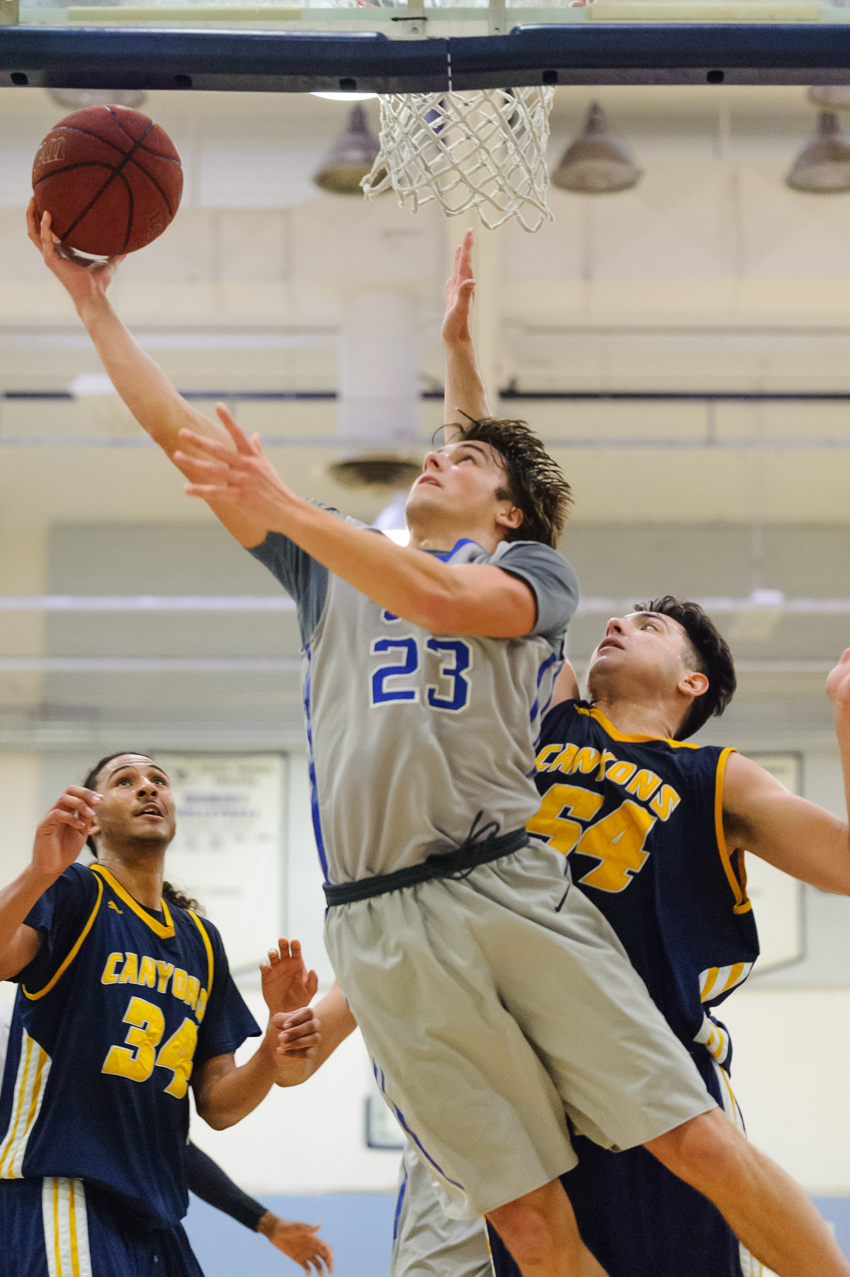 Forward Dayne Downey (23,Middle) of Santa Monica College goes up for a reverse layup while guarded by Anthony Simone (54,Right) of the College of the Canyons. The Santa Monica College Corsairs lose the game 74-72 to the College of the Canyons Cougars. The game was held at the SMC Pavilion at the Santa Monica College Main Campus in Santa Monica, Calif.. February 10, 2018. (Photo by: Justin Han/Corsair Staff)