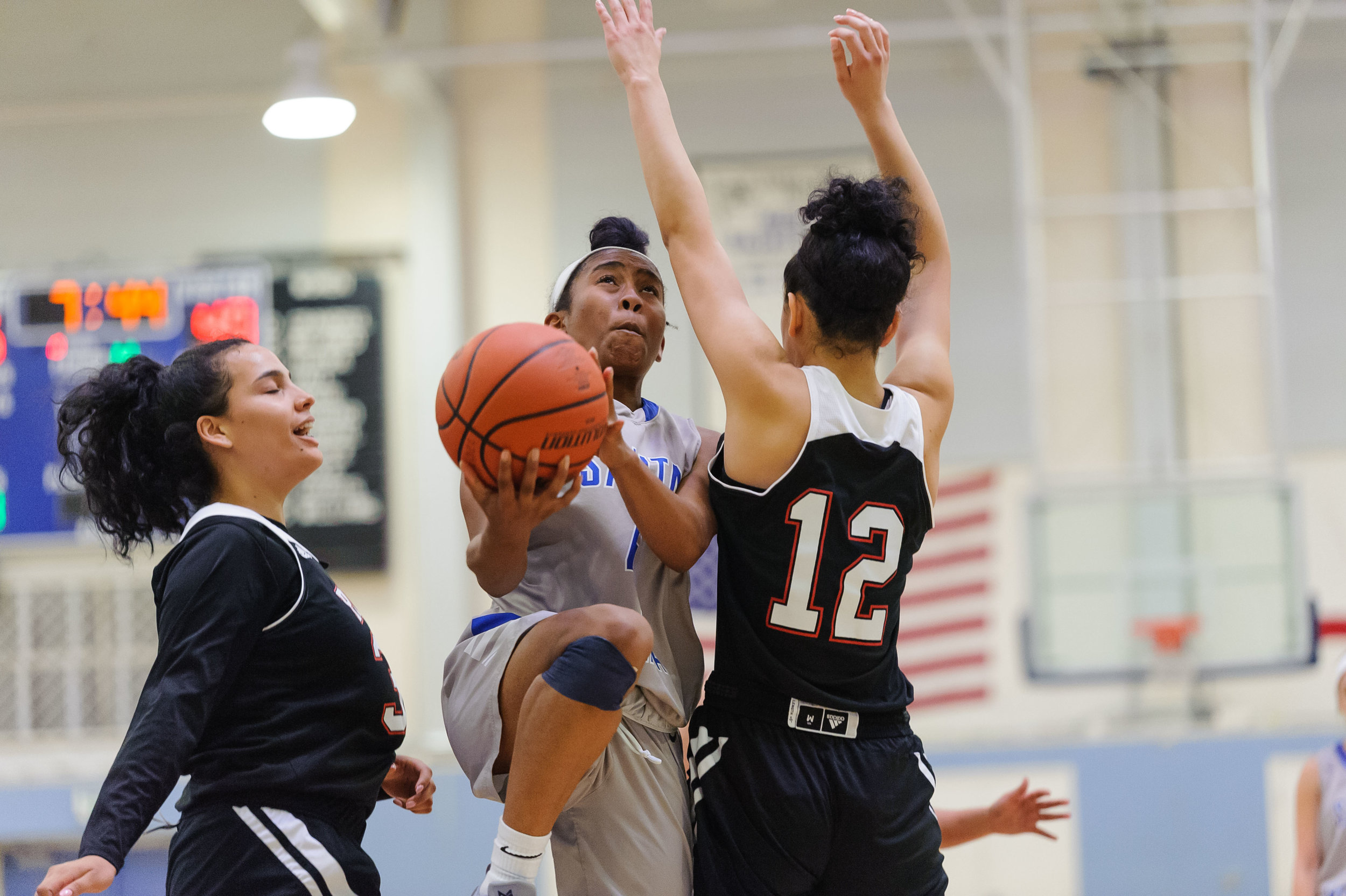 Guard Lisa Hall (4,Middle) of Santa Monica College goes up for a layup while contested by Adriana Penate (12,Right) of Pierce College. The Santa Monica College Corsairs win their final game of the season 76-53 against the Pierce College Brahmas. The game was held at the SMC Pavilion at the Santa Monica College Main Campus in Santa Monica, Calif.. February 17, 2018. (Photo by: Justin Han/Corsair Staff)