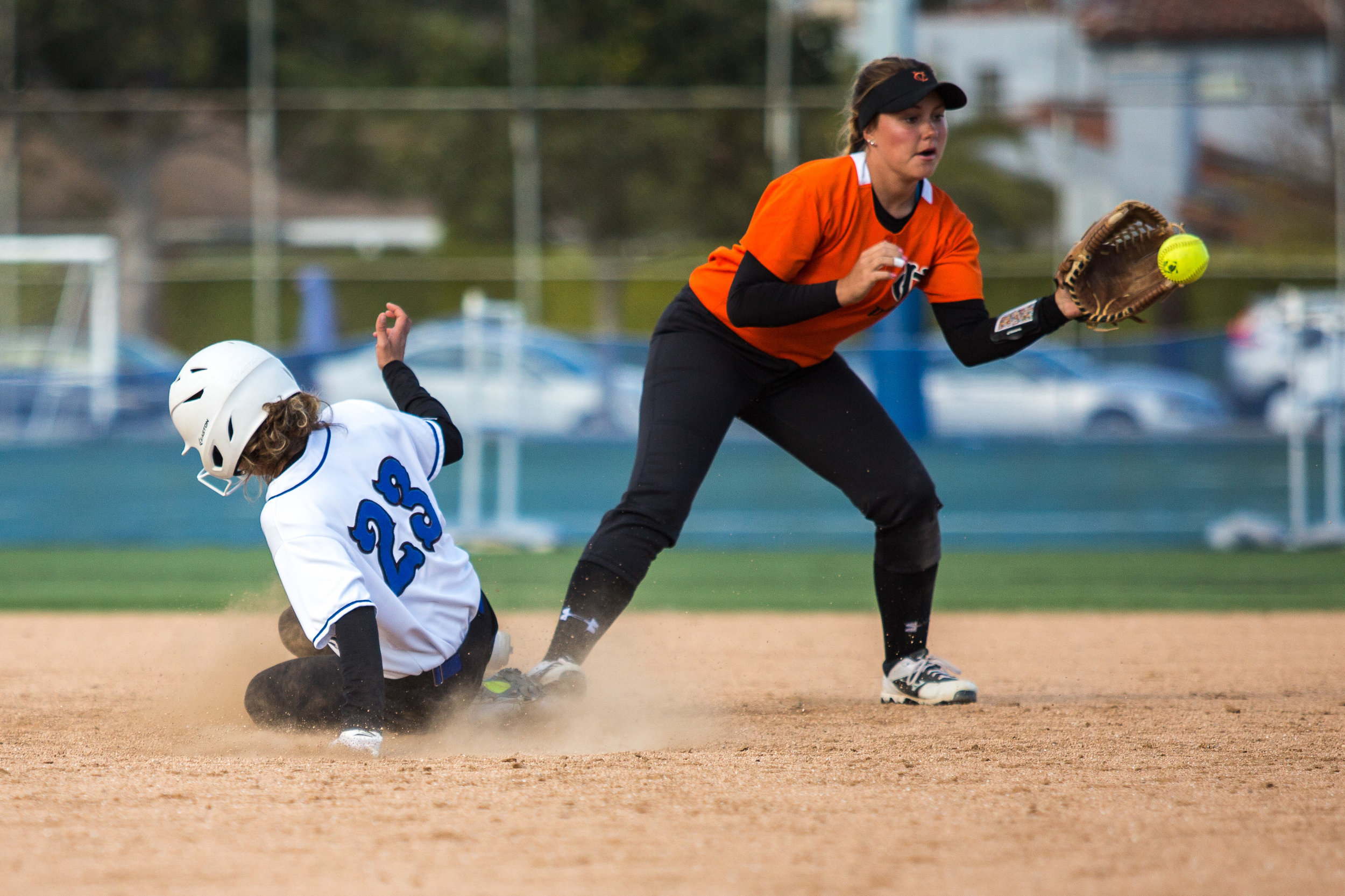 Santa Monica College Corsair freshman Taylor Liebesman #23 (left, white) successfully slides into 2nd base as Ventura College Pirate freshman second short stop Danielle Carmona #13 (right, red) receives the ball from in-field during the bottom of the third at the Corsair Field in Santa Monica, California, on Tuesday, February 28, 2017. The Corsairs would go on to lose the game 0-14 against the Ventura College Pirates. (Corsair Photo: Matthew Martin)