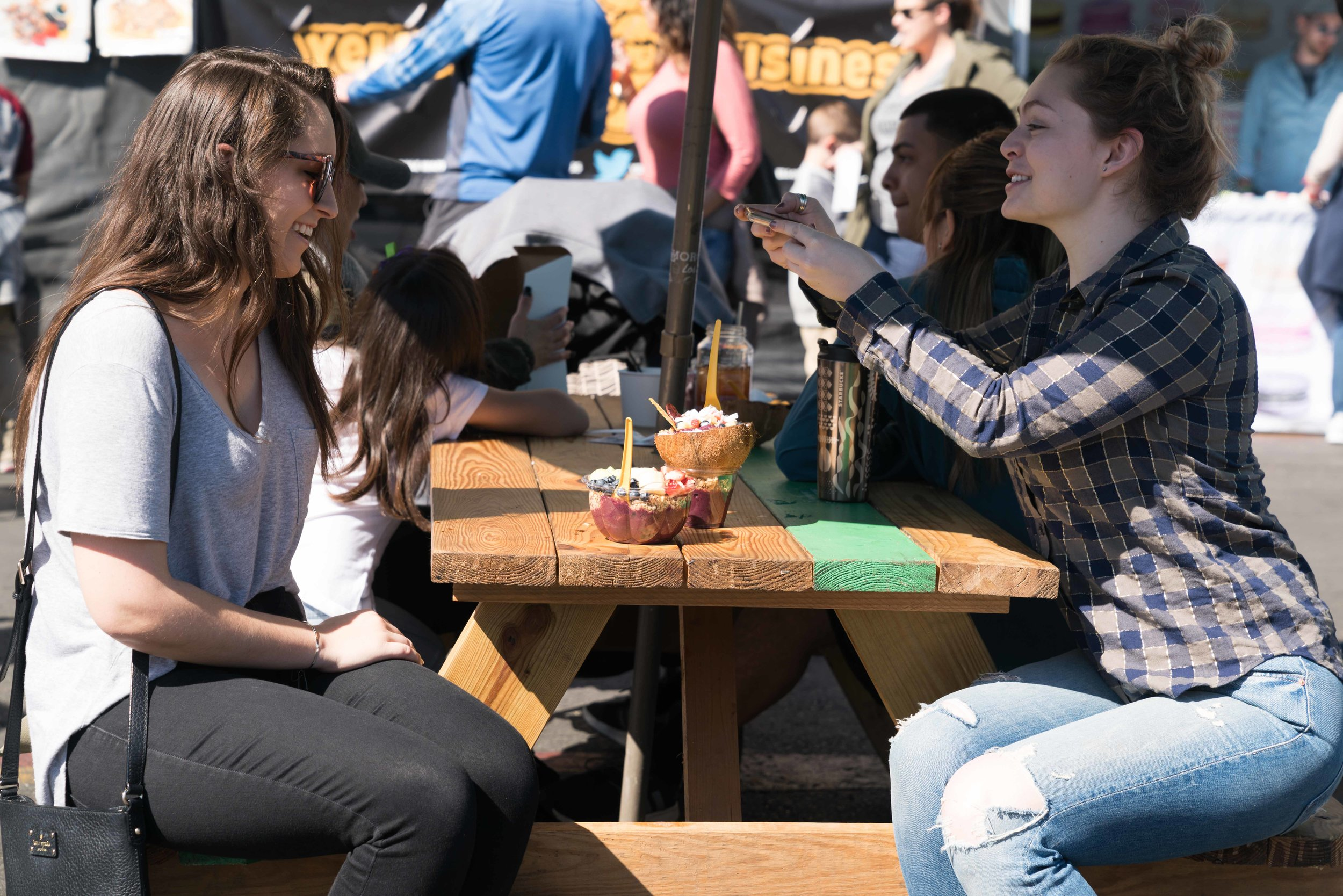 Amanda Slate (right) and Erika VonNovak (left) takes pictures of their coconut bowls from Amazeballs on Sunday, February 25, 2018 at Smorgasburg LA, a weekly food and vendor market on Sundays at Row DTLA. (Photo by Helena Sung)