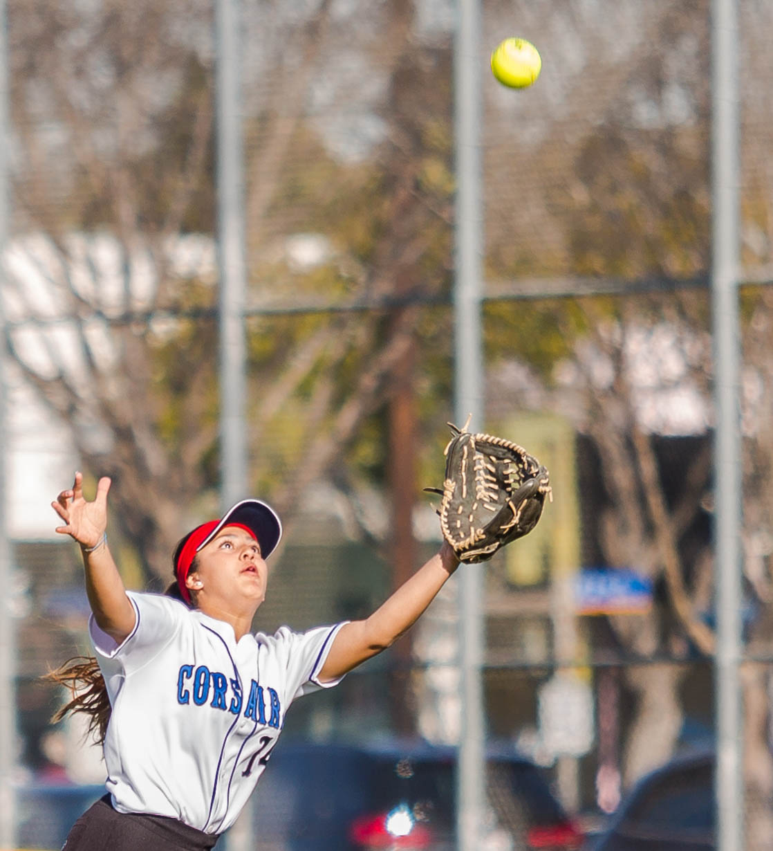 Santa Monica College Corsair freshman outfielder Jen Baca #14 focuses as she reaches for the ball in the outfield, which is hit by a Bakersfield College Renegade's batter Alexis Solis #17(not shown) during the bottom of the 3rd inning at the Santa Monica College Corsair Field in Santa Monica California, on Tuesday, March 6, 2018. Baca would successfully catch the ball, ending the inning for the Bakersfield College Renegades, sending the Corsairs back in to bat at the top of the 4th inning. However, the Corsairs would go on to lose the game 0-9 to the Bakersfield College Renegades, making the Corsairs tally for the season 6 wins and 11 losses. (Corsair Photo: Matthew Martin)