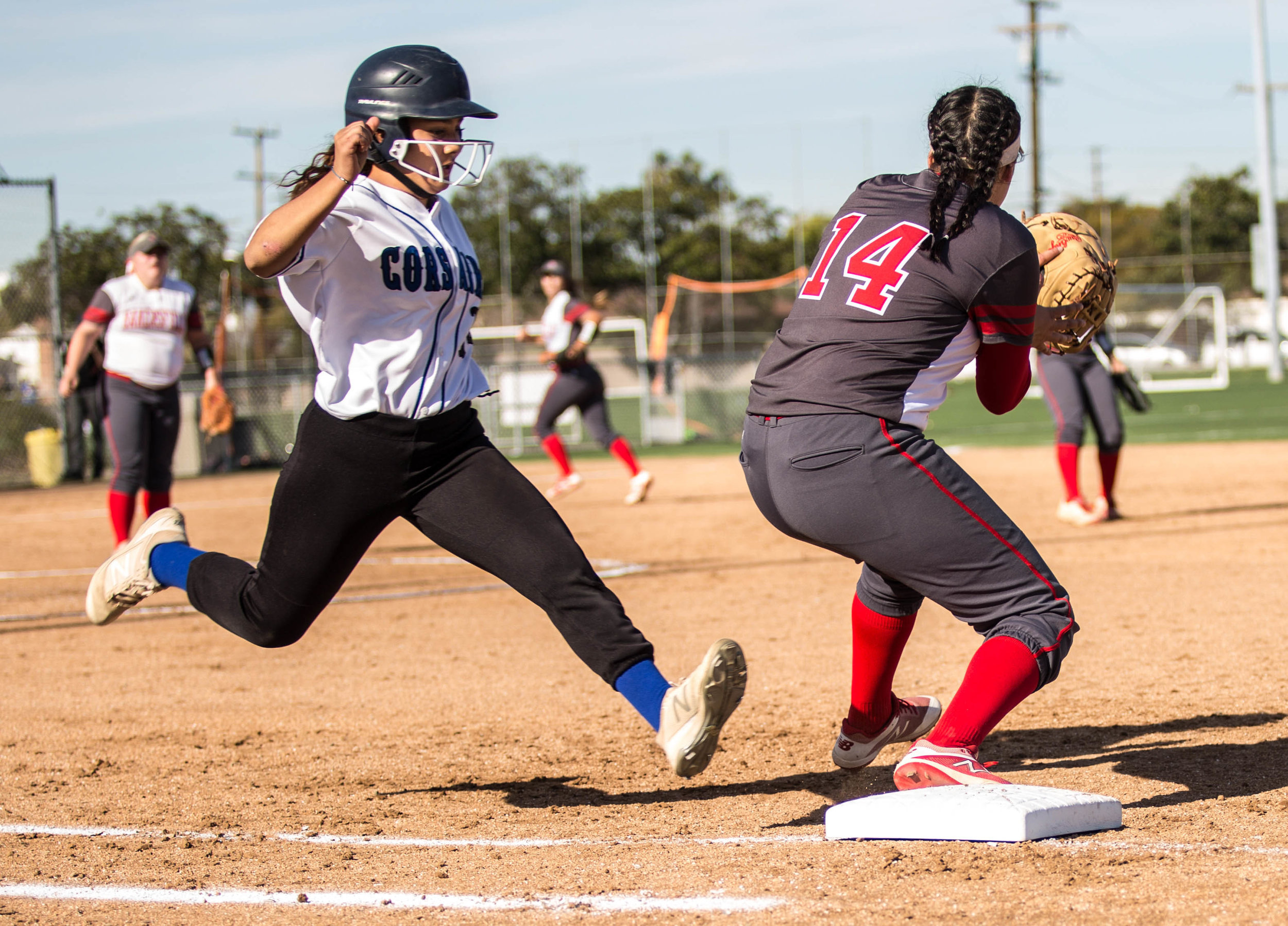 Santa Monica College Corsair freshman batter Jen Baca #14 (left, white) successfully takes first base as Bakersfield College Renegade sophomore infielder Aryka Chavez #14 (right, red) fails to tag Baca, who is declared safe, during the top of the 5th inning at the Santa Monica College Corsair Field in Santa Monica California, on Tuesday, March 6, 2018. The Corsairs would go on to lose the game to Bakersfield College 0 – 9, making their tally for the season 6 wins and 11 losses. (Corsair Photo: Matthew Martin)