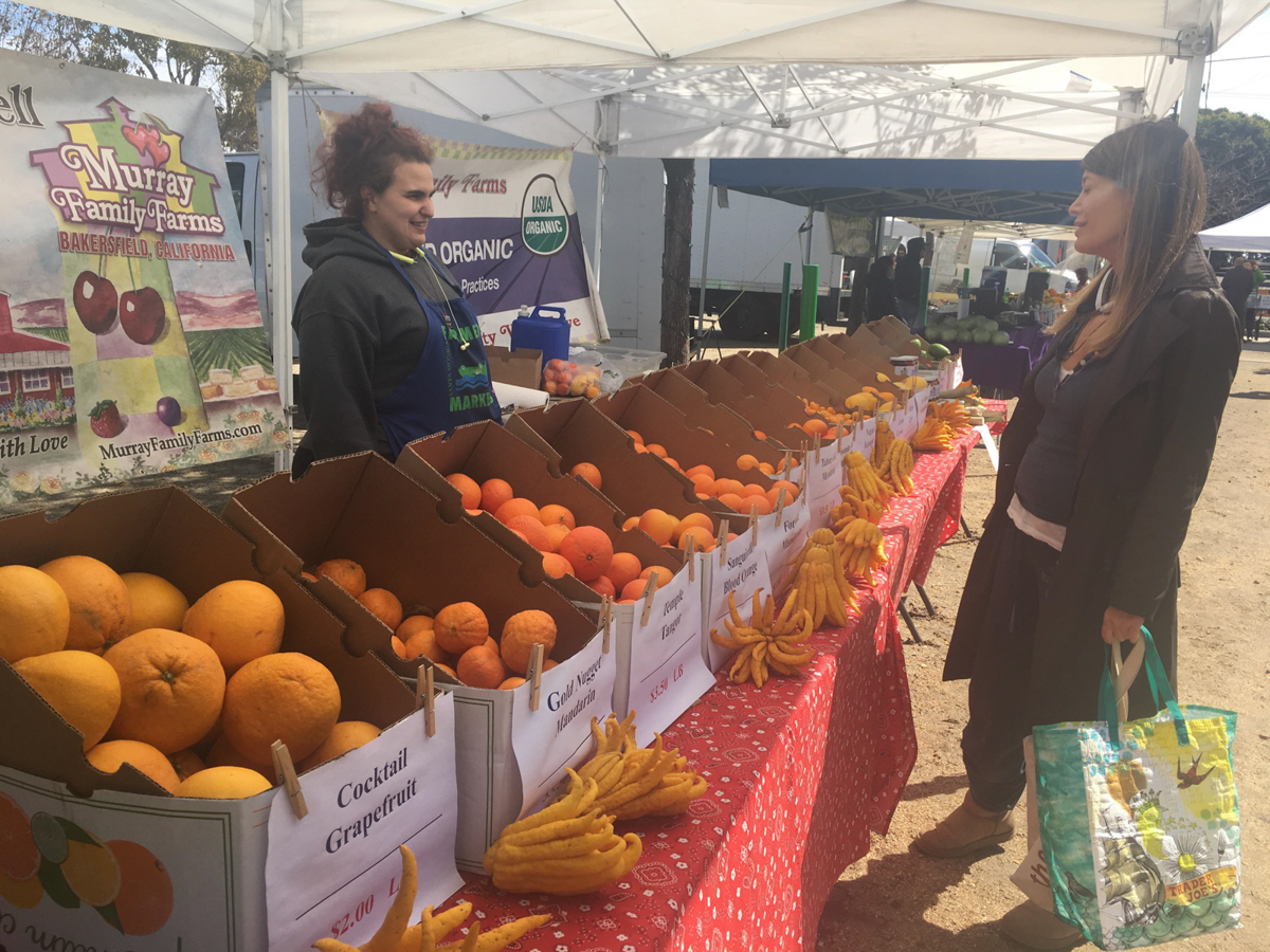 Murray Family Farm employee Jazz Bodi (left) taking care of a customer and explaining the different types of exotic citrus fruits they offer at the Santa Monica farmers market in Virginia Avenue Park in Santa Monica, Calif. on March 3, 2018.  (Photo by: Claudia Vardoni)