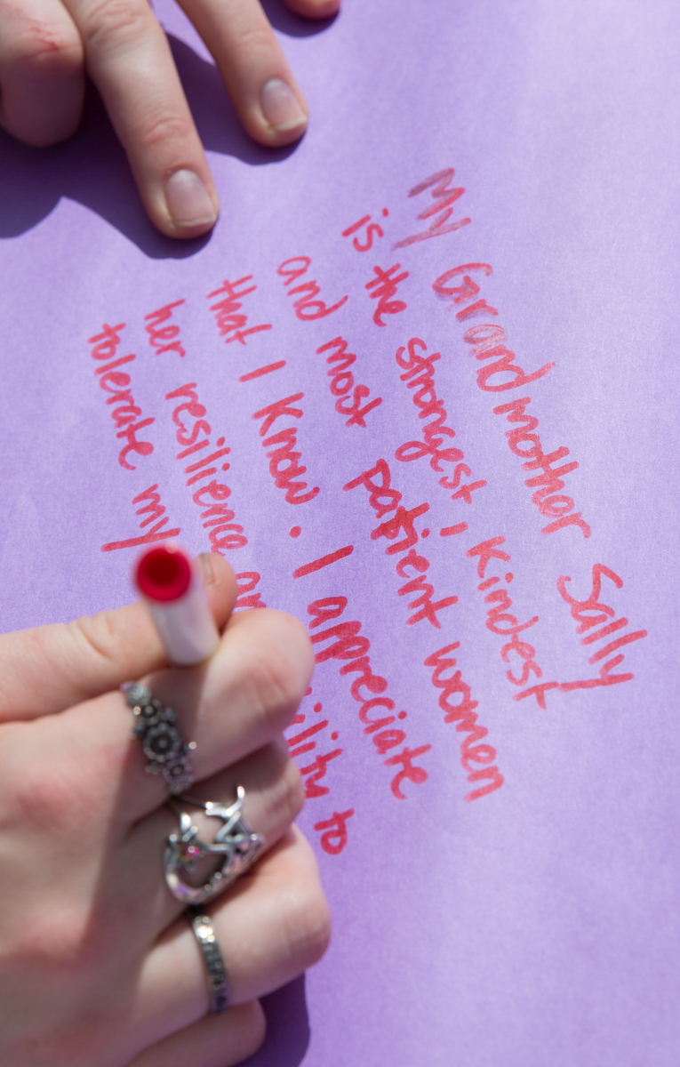 An attendee of the Santa Monica College International Women's Day event takes part in the festivities by writing about the women in their life that inspire on purple paper, a universal color that represents all women, during the SMC International Women's Day event that took place on the SMC main campus, in front of the Library Walkway, in Santa Monica California on Thursday, March 8, 2018. The Women's Day event welcomed all students to share inspirational stories about the inspirational women in their lives, and in the SMC community. (Corsair Photo: Matthew Martin)