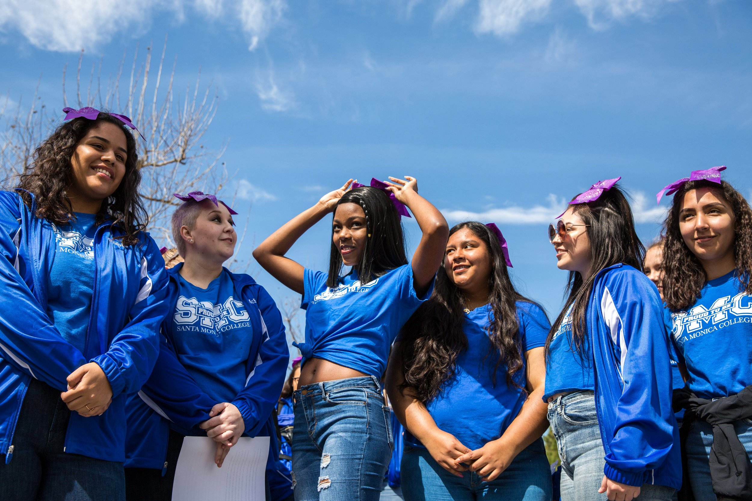 Members of the Santa Monica College cheer squad put on their purple bows with pride during the Santa Monica College International Women's Day event that took place on the SMC main campus, in front of the Library Walkway, in Santa Monica California on Thursday, March 8, 2018. Internationally, the color purple that the women are wearing signifies dignity and justice and is a color that is universal in representing all women. (Corsair Photo: Matthew Martin)