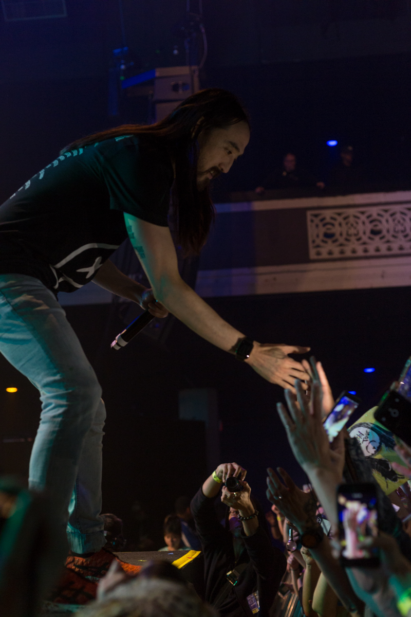 Electronic music artists and DJ Steve Aoki runs to the front of the stage to high five fans in the front row at the Shrine Expo Hall and Auditorium in Downtown LA in Los Angeles, California on Friday, March 9th 2018.  DJ Steve Aoki is currently on tour as part of his Kolony Tour. (Photo by: Thane Fernandes)