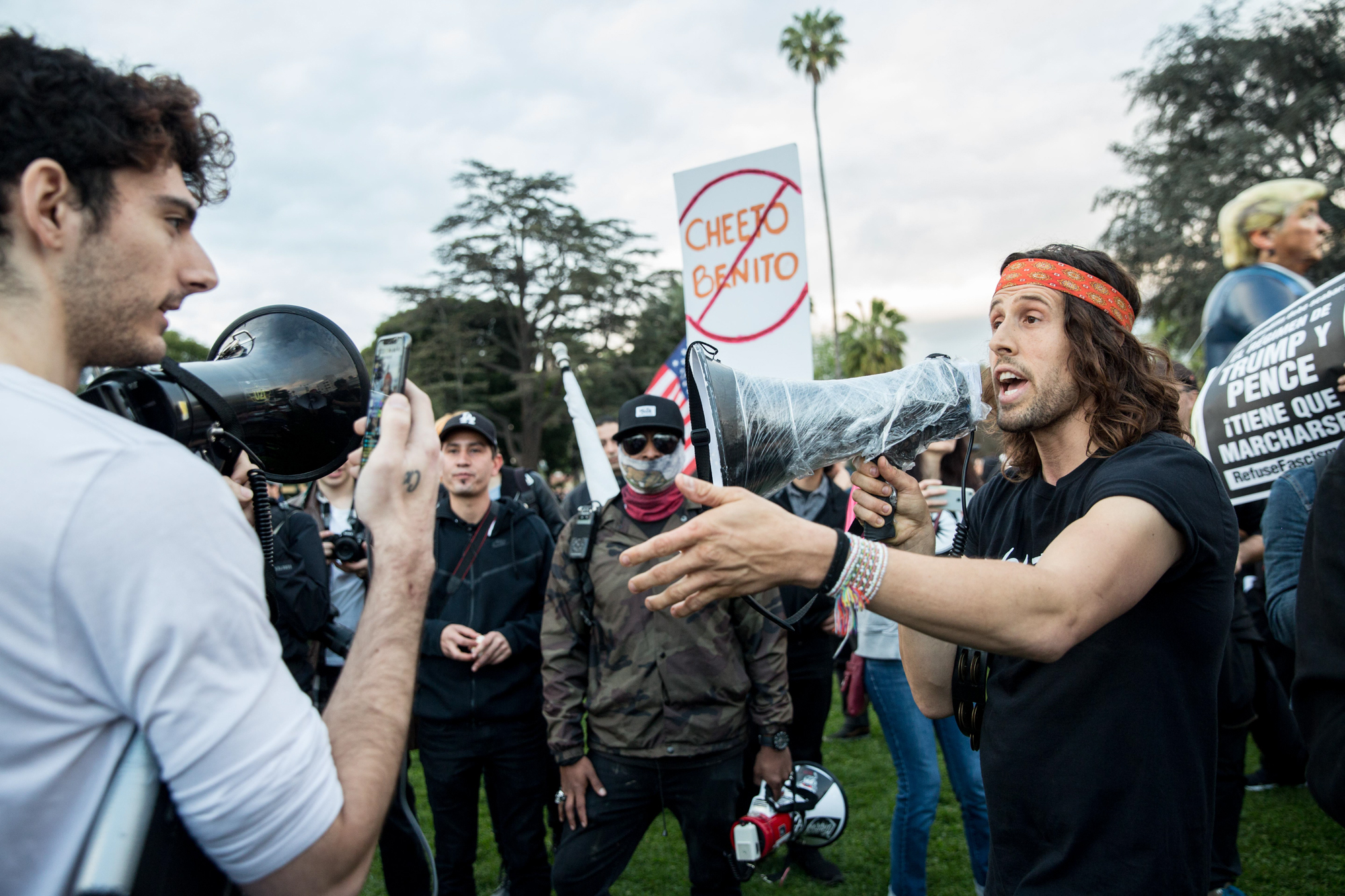 Revolution LA member and anti Trump supporter Daniel McCollister (right) tries having a discussion over the megaphone with an anti-Trump supporter (left) during the Los Angeles Anti-Trump rally that took place in Beverly Gardens Park, in Beverly Hills California on Tuesday, March 13, 2018. As President Donald Trump made his way to a fundraiser in Beverly Hills, protesters were there to greet him with their dissent during Tuesdays protest. (Photo by: Matthew Martin)