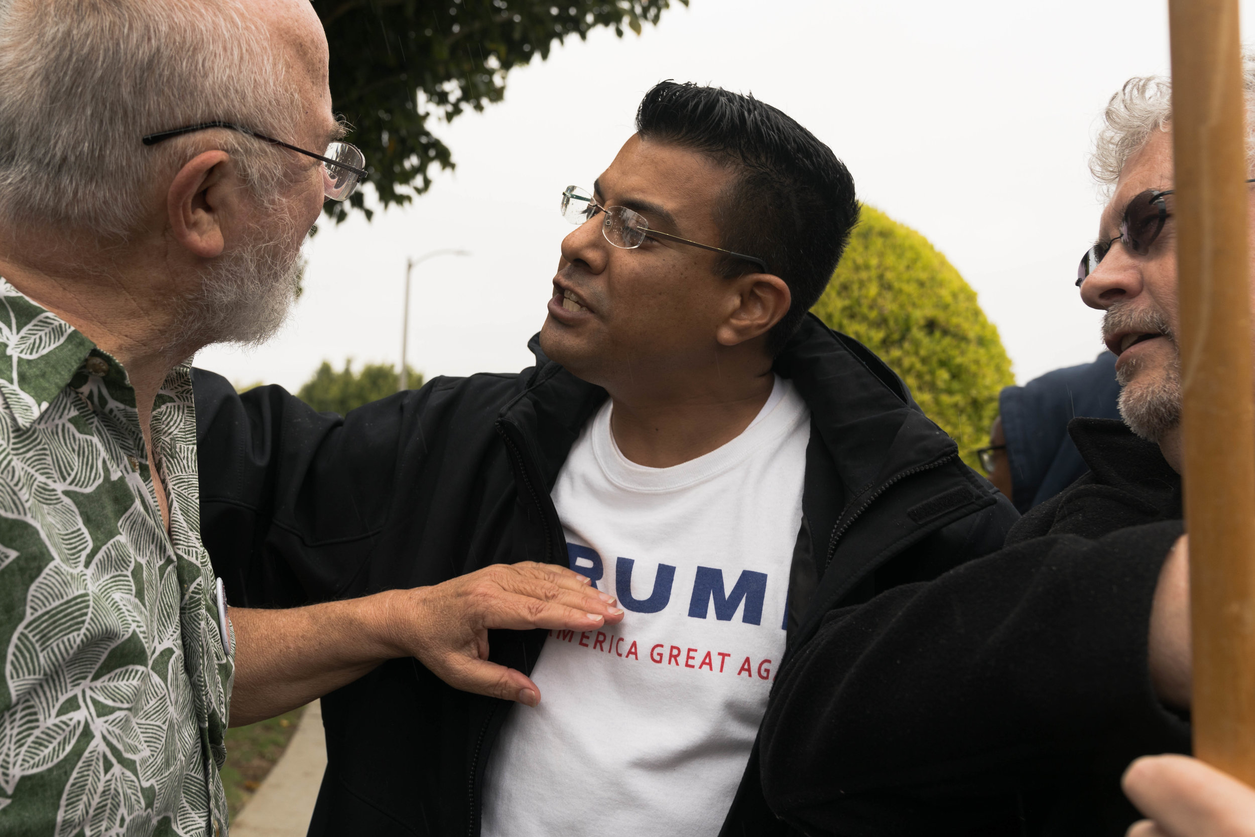 """Danny Rodriguez (center), a Trump supporter, drove from Fontana to confront the protesters in Santa Monica, California on Tuesday, March 13, 2018. """"I'm here to try to change minds,"""" he said. """"I'm here by myself to take on everybody. If this country falls, the whole world falls. Real democracy comes from borders."""" (Helena Sung / Corsair Photo)"""
