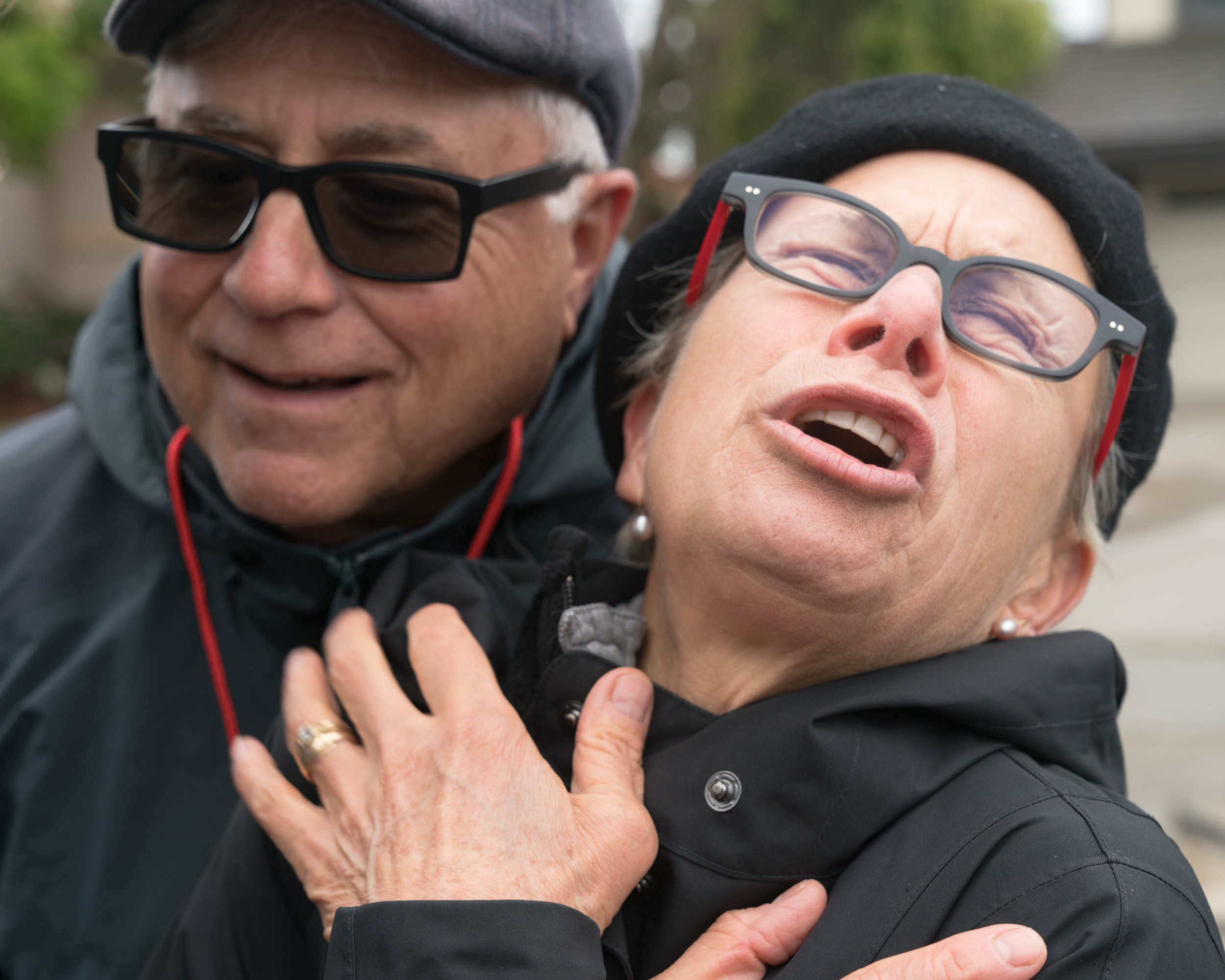 """Kim Cheselka (right) and her husband Mitch Dubin (left) came to protest President Trump's arrival in Santa Monica, California on Tuesday, March 13, 2018. Cheselka grimaced as she recalled seeing Trump wave at the crowd as he drove by in his motorcade. """"I'm so grossed out,"""" Cheselka said. """"You see him on TV, but to actually see him in person I had a visceral response and it was negative."""" """"You yelped,"""" her husband said. """"You said you weren't going to be able to sleep tonight."""" (Helena Sung / Corsair Photo)"""