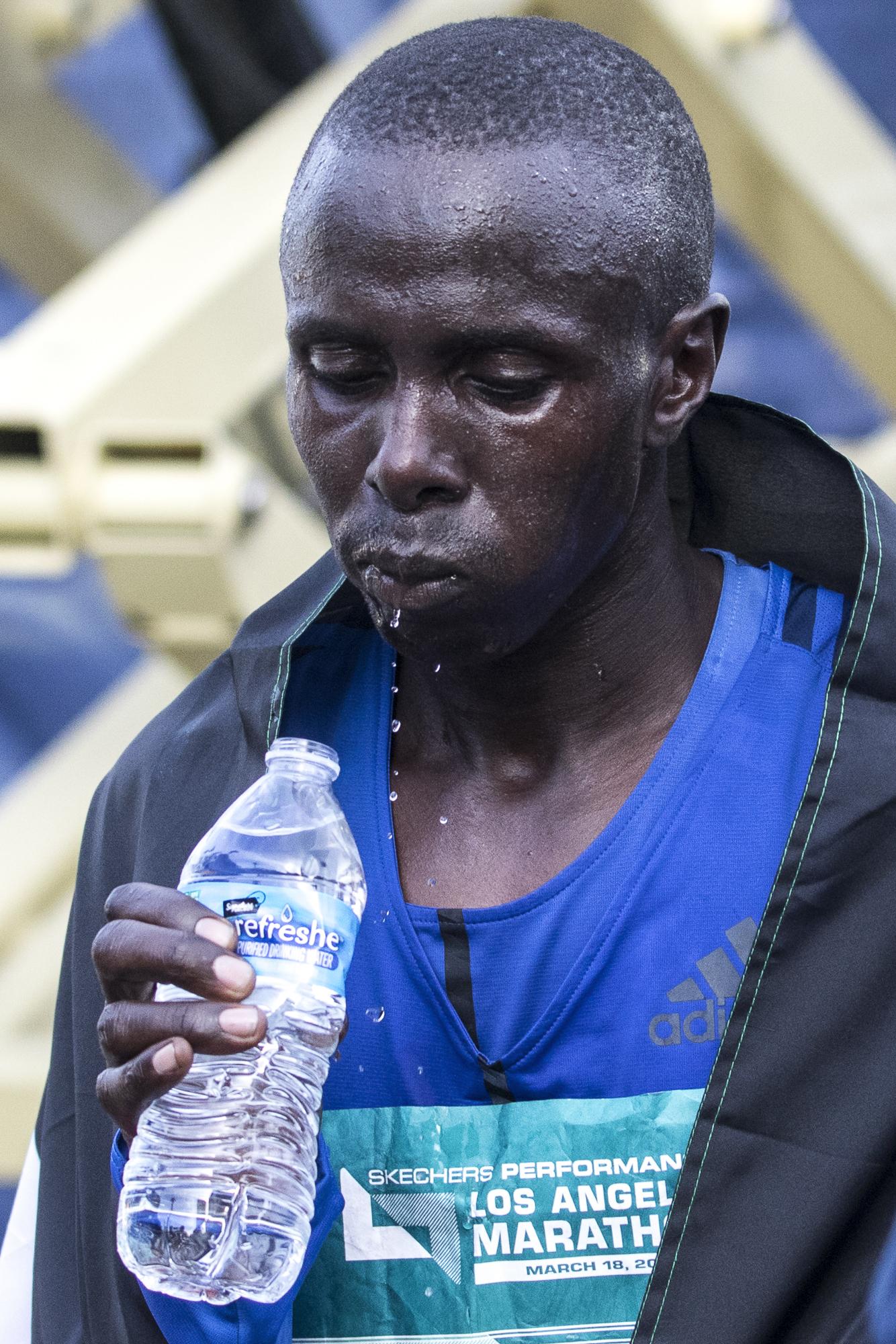 Elisha Barno gets a drink of water after finishing third in the 2018 Los Angeles Marathon on March 18, 2018 in Santa Monica, California. (Zane Meyer-Thornton/Corsair Photo)