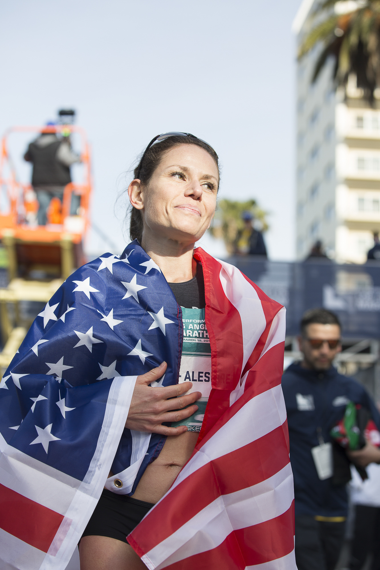 Los Angeles Marathon competitor Christina Vergara-Aleshire drapes her US flag around her after coming in fourth-place during the pro women's LA marathon event  on March 18, 2018 in Santa Monica, California. Aleshire received the best finish by an American woman, coming in with a fourth-place with a race time of 2:34.24. (Matthew Martin/Corsair Photo)