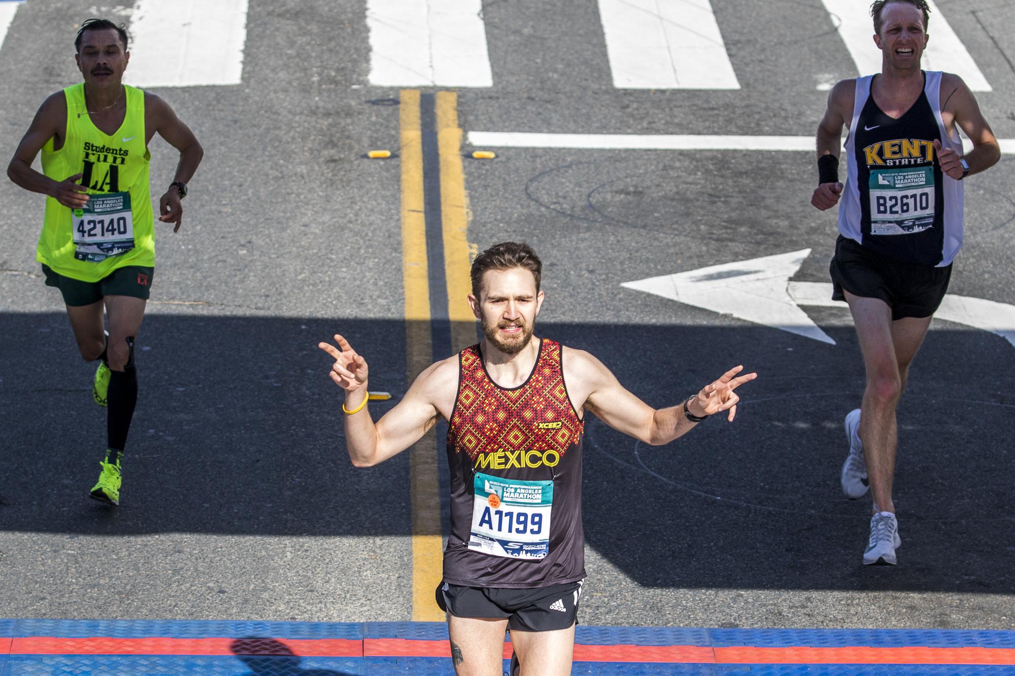 Armando Osorio (middle), Jose Jimenez (left), and Ben Wietmarschen (right) finishing the 2018 Los Angeles Marathon on March 18, 2018 in Santa Monica, California. (Zane Meyer-Thornton/Corsair Photo)