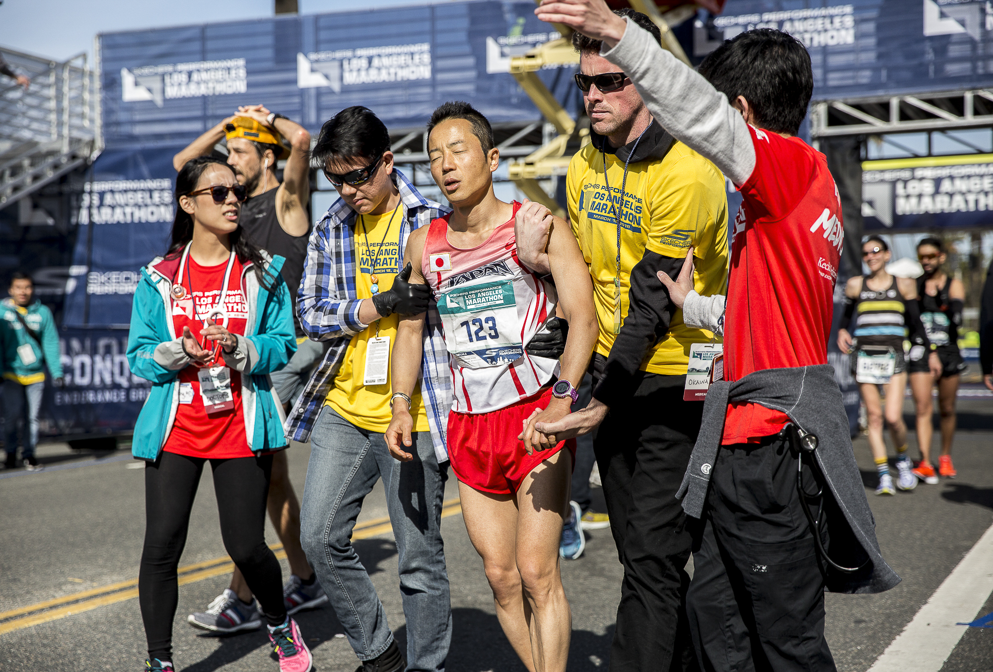 """Koji Kawamoto (bib #123) receives help from """"Hotwalkers"""" after finishing the 2018 Los Angeles Marathon with a total race time of 3:11:40 on March 18, 2018 in Santa Monica, California. """"Hotwalkers"""" are Los Angeles Marathon volunteers who escort runners to the medical tent after finishing the event if they are showing signs of ill health. (Matthew Martin/Corsair Photo)"""