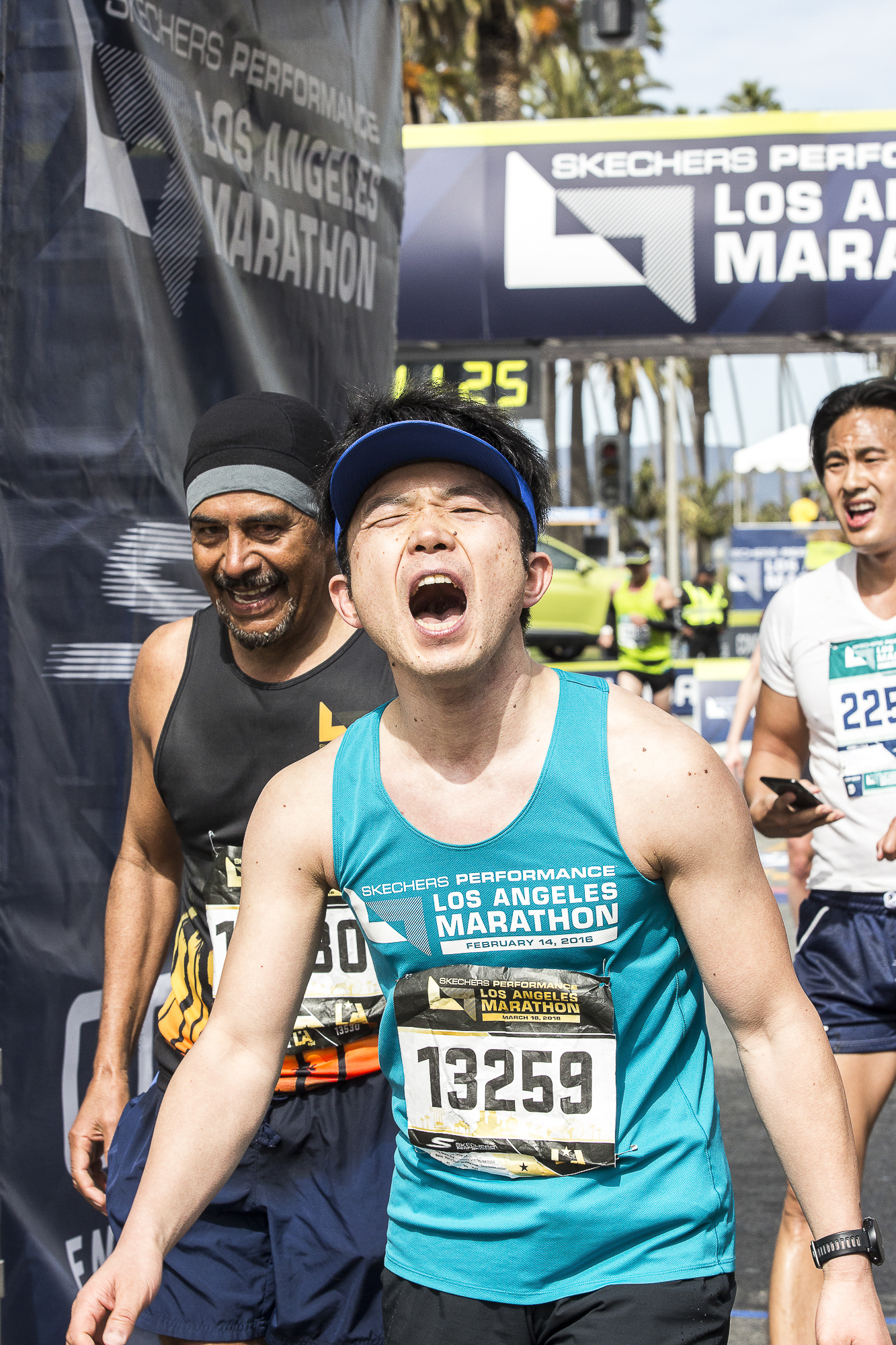 """Toshihiko Tateshita (bib #13259) (center) screams with joy after completing the 33rd annual Los Angeles Marathon event with a final time of 3:52:36 in Santa Monica, California on Sunday March 18, 2018. """"I did it…I finally did it! And no one can take that away from me!"""" Tateshita loudly stated. (Matthew Martin/Corsair Photo)"""