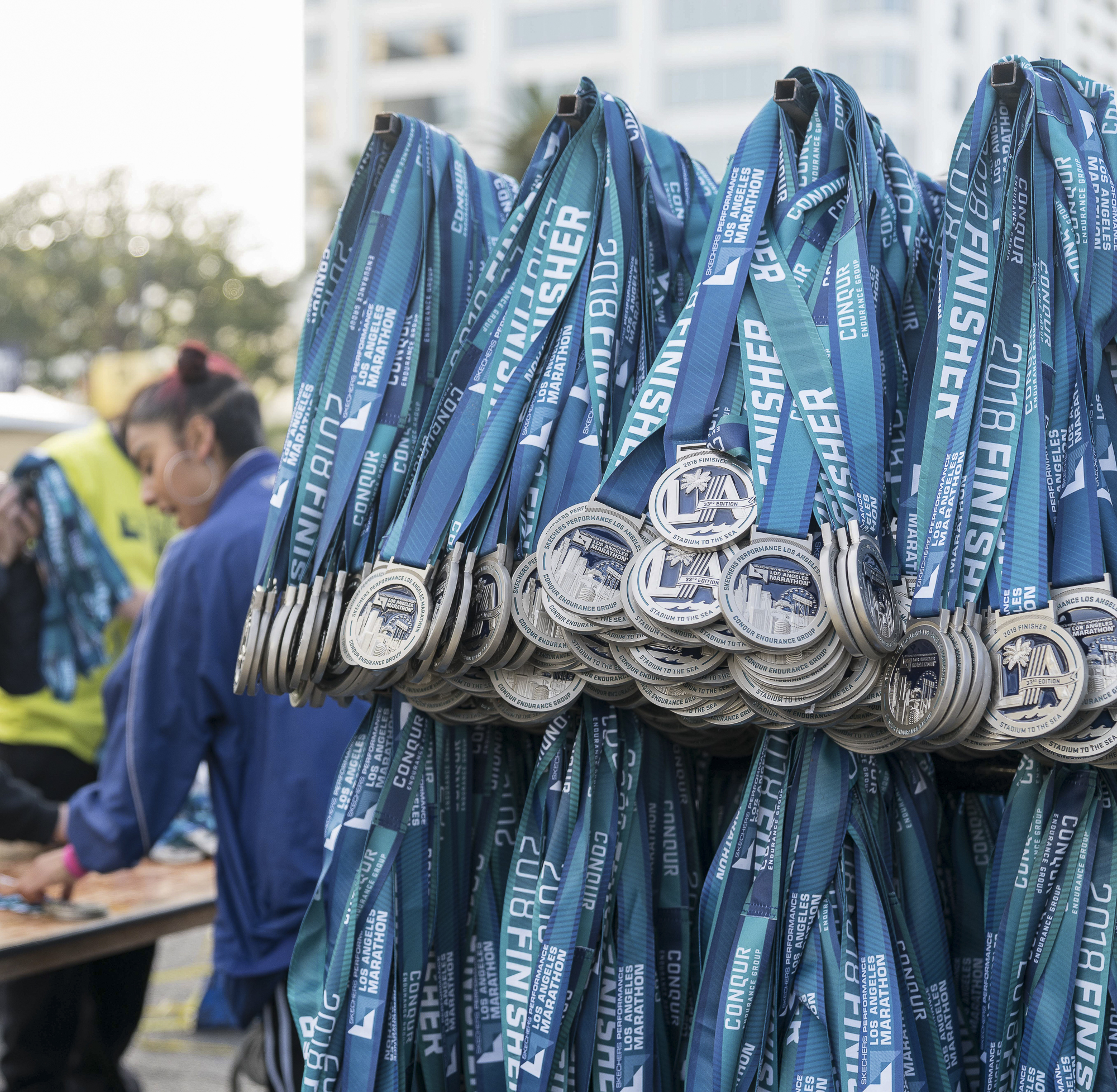 Los Angeles Marathon volunteer, Karen Arriola, unboxes and hangs medals in Santa Monica, California on Sunday, March 18, 2018. It is estimated that 24,000 people participated in the marathon this year. (Photo by: Helena Sung).