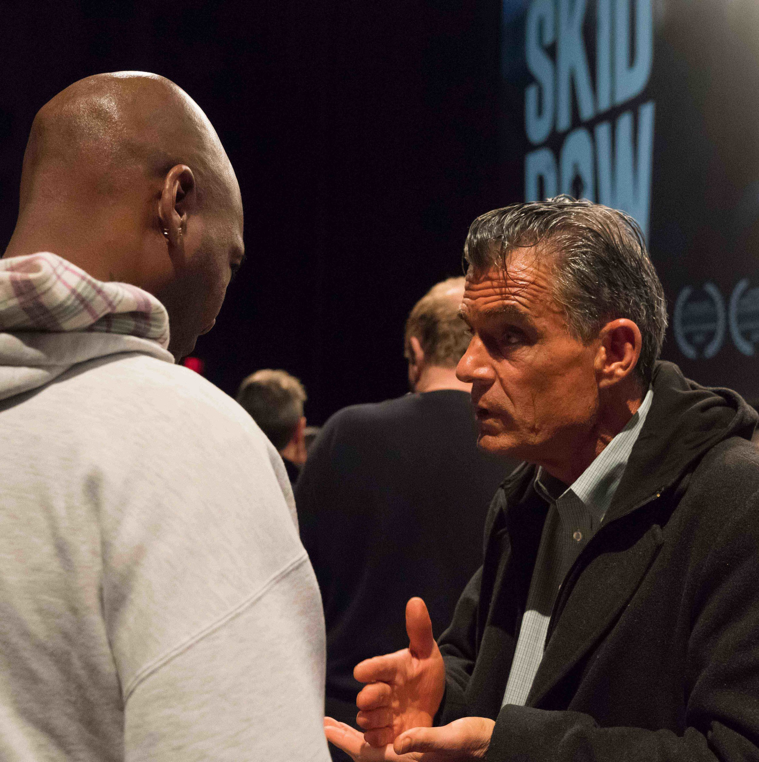 """Elijah Muhammad (left) approaches Judge Craig Mitchell (right) after a screening of the documentary, Skid Row Marathon, in Los Angeles, California on March 16, 2018. Muhammad asked the judge how he could join the Skid Row Running Club. """"Just show up,"""" said Judge Mitchell, telling Muhammad the days and time of their weekly training runs that meet at the Midnight Mission homeless shleter on Skid Row. (Helena Sung/Corsair Photo)"""