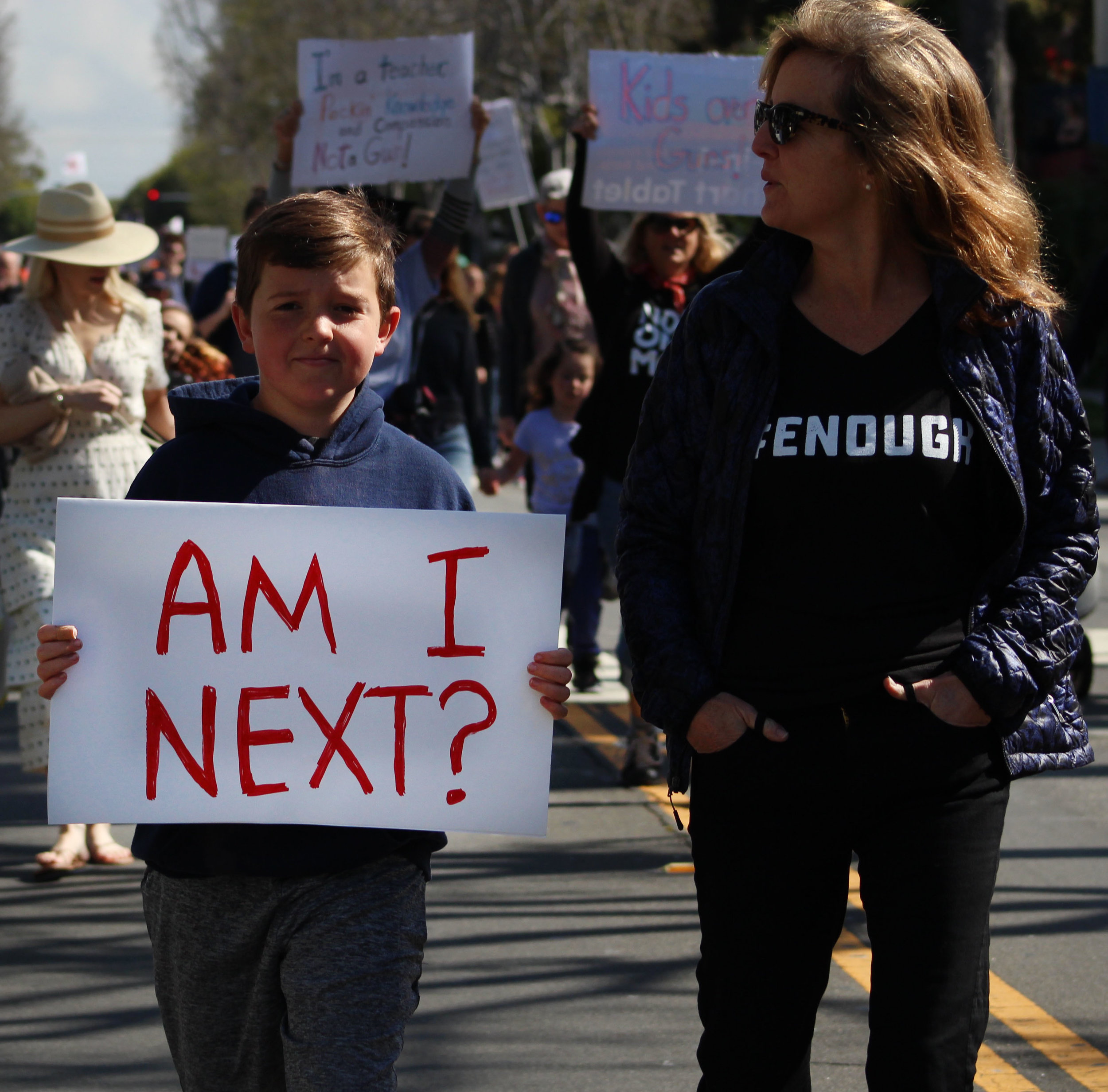 Jack Schneider and his mom, Laura Scheider, walk within the crowd holding homemade signs and chanting along with the protest on Montana Avenue in Santa Monica, California. On Saturday, March 24, 2018. (Pyper Witt/Corsair Photo)