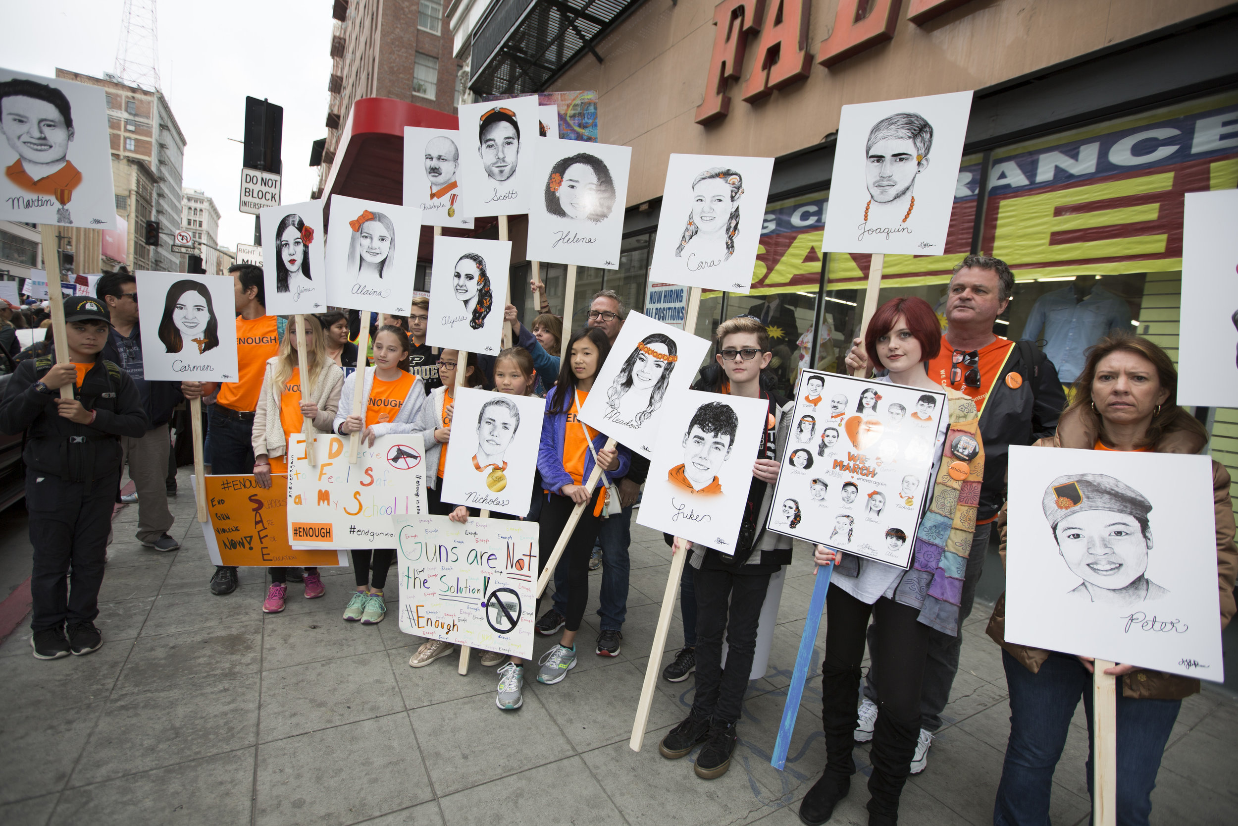 A group of young students, and parents, stand on 5th and Broadway in downtown Los Angeles holding art posters of the 14 fallen students from Majory Stoneman Douglas High School, before marching to City Hall during the March for Our Lives rally on March 24, 2018, in Los Angeles, California. (Daniel Bowyer/Corsair Photo)