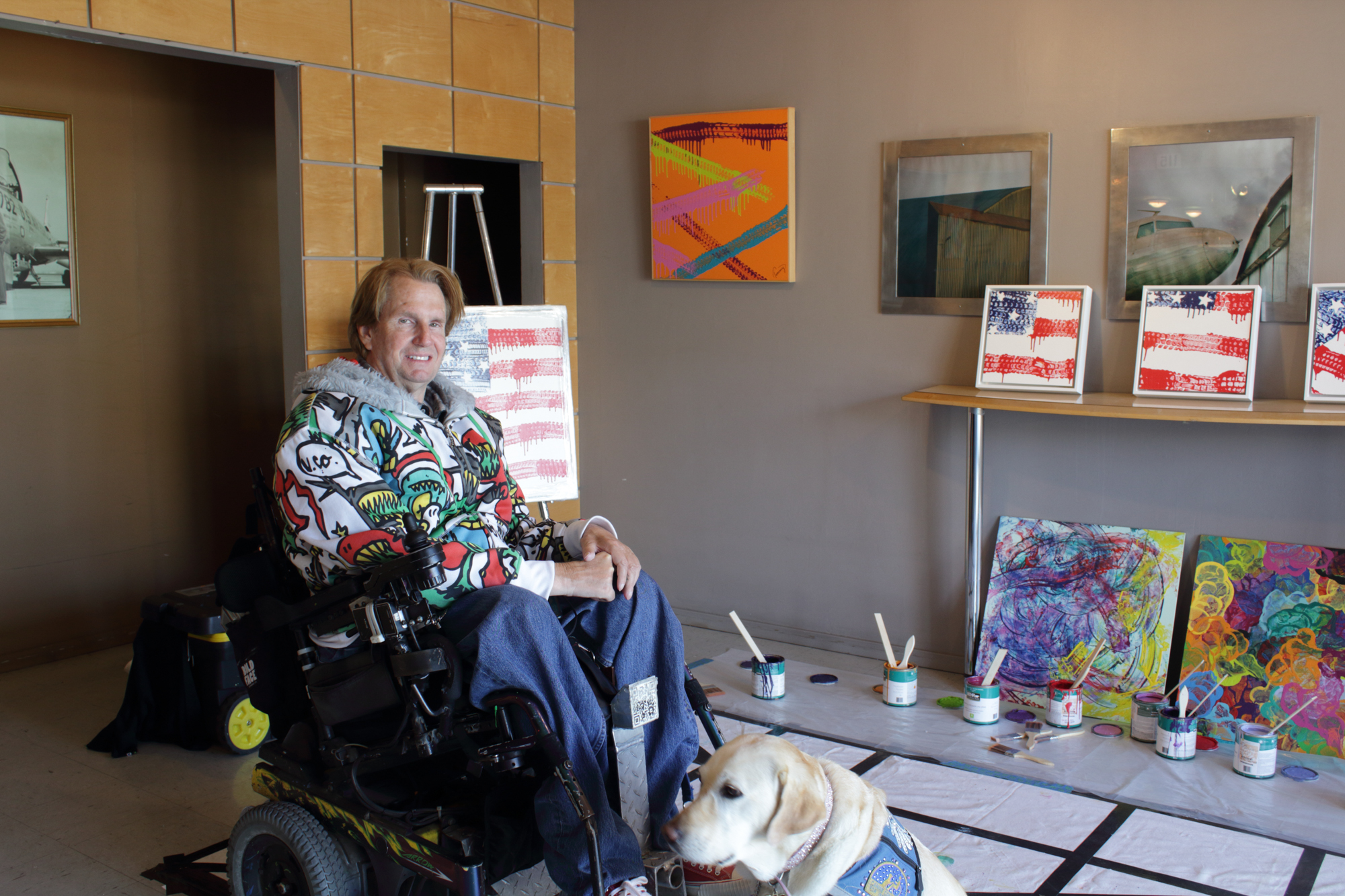 Tommy Hollenstein, wheelchair-bound quadriplegic artist, poses with his artwork made with the wheels of his wheelchair and service dog at the 12 Annual Santa Monica ArtWalk on March 24th, 2018 in Santa Monica, California. (Heather Creamer/ Corsair Photo)