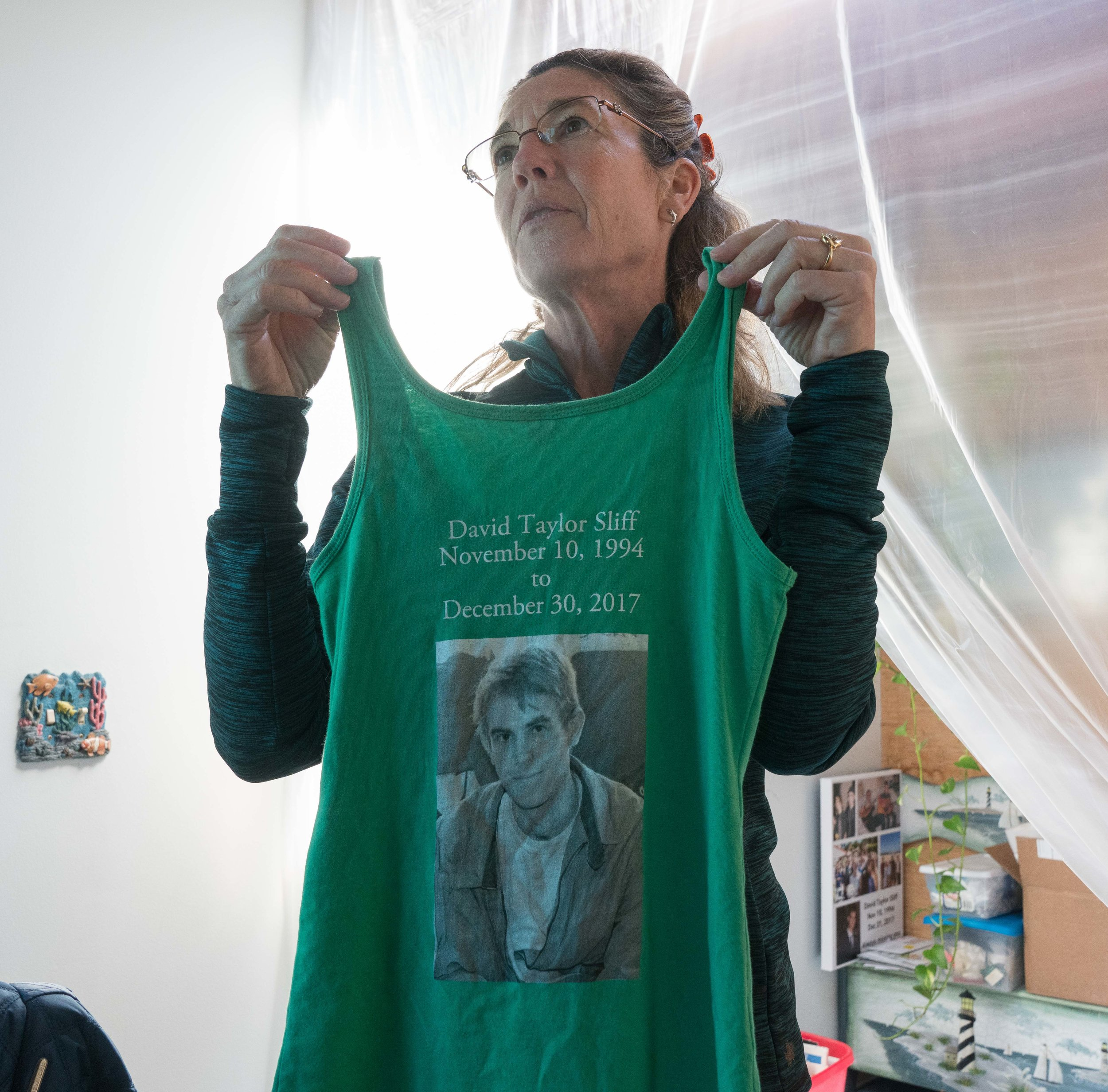 Kathy Welch holds up a tank top she had made honoring her son, fomer SMC student David Sliff, at her home in Hermosa Beach, Calfifornia on Saturday, March 17, 2018. Welch wore a blue version of the tank top when she ran the Los Angeles Marathon the nexxt day. (Helena Sung/Corsair Photo)