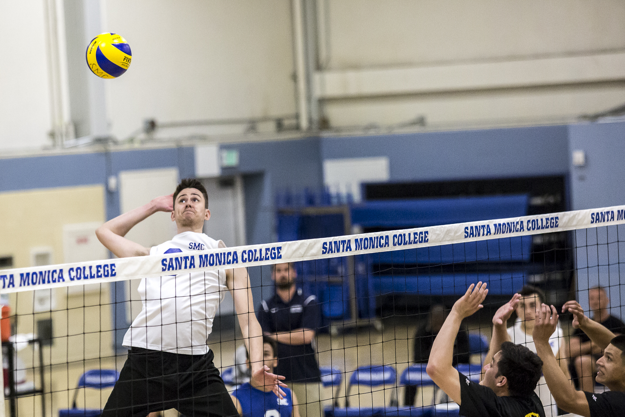 Santa Monica College Corsair middle-hitter Nick Kostetsky #8 (left, white) leaps in the air to hit a very powerful spike into the defense of the Los Angeles Trade Tech Beavers during the Corsairs 3-0 blowout victory against the Tech Beavers in the Santa Monica College (SMC) Pavilion at the SMC main campus in Santa Monica California, on Friday, March 30 2018. (Matthew Martin/Corsair Photo).