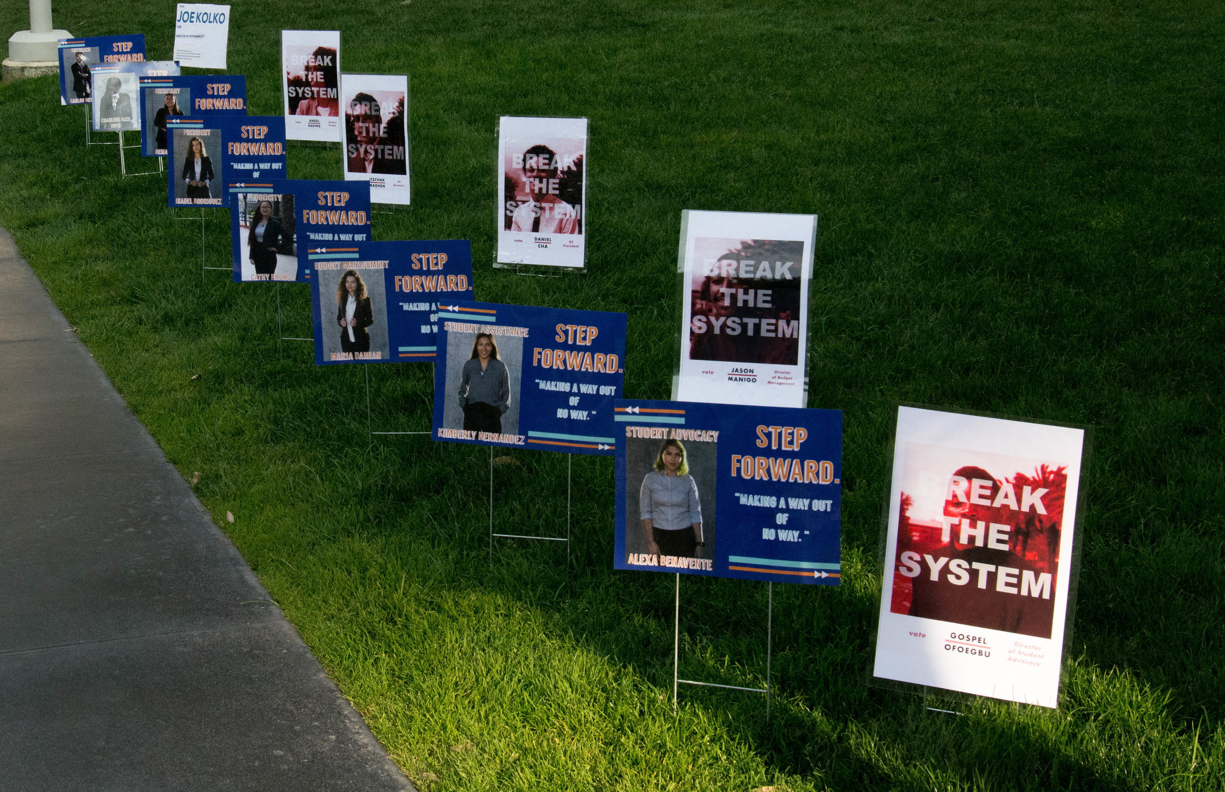 """Campaign advertisements line the main quad at Santa Monica College in Santa Monica, California. Posters from the Slate """"For the Students"""" are absent due to their slate not being informed about a recent change to the election code waiving a stamp requirement for printed campaign material. (Reed Curtis/Corsair Photo)"""