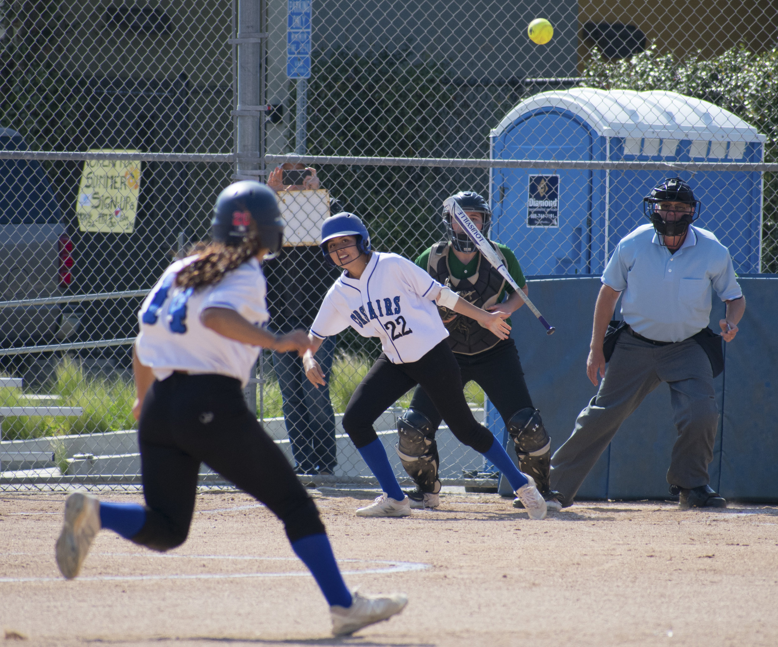 Santa Monica Corsair Erika Soto (#22) proceeds to run to second base after striking as Jen Baca (#14) runs to third during a softball game against the Cuesta College Cougars on Tuesday, April 4 at the John Adams Middle School Field in Santa Monica, California. It was a close 10-inning game, which ended in a 6-5 loss for the Corsairs. (Ethan Lauren/Corsair Photo)