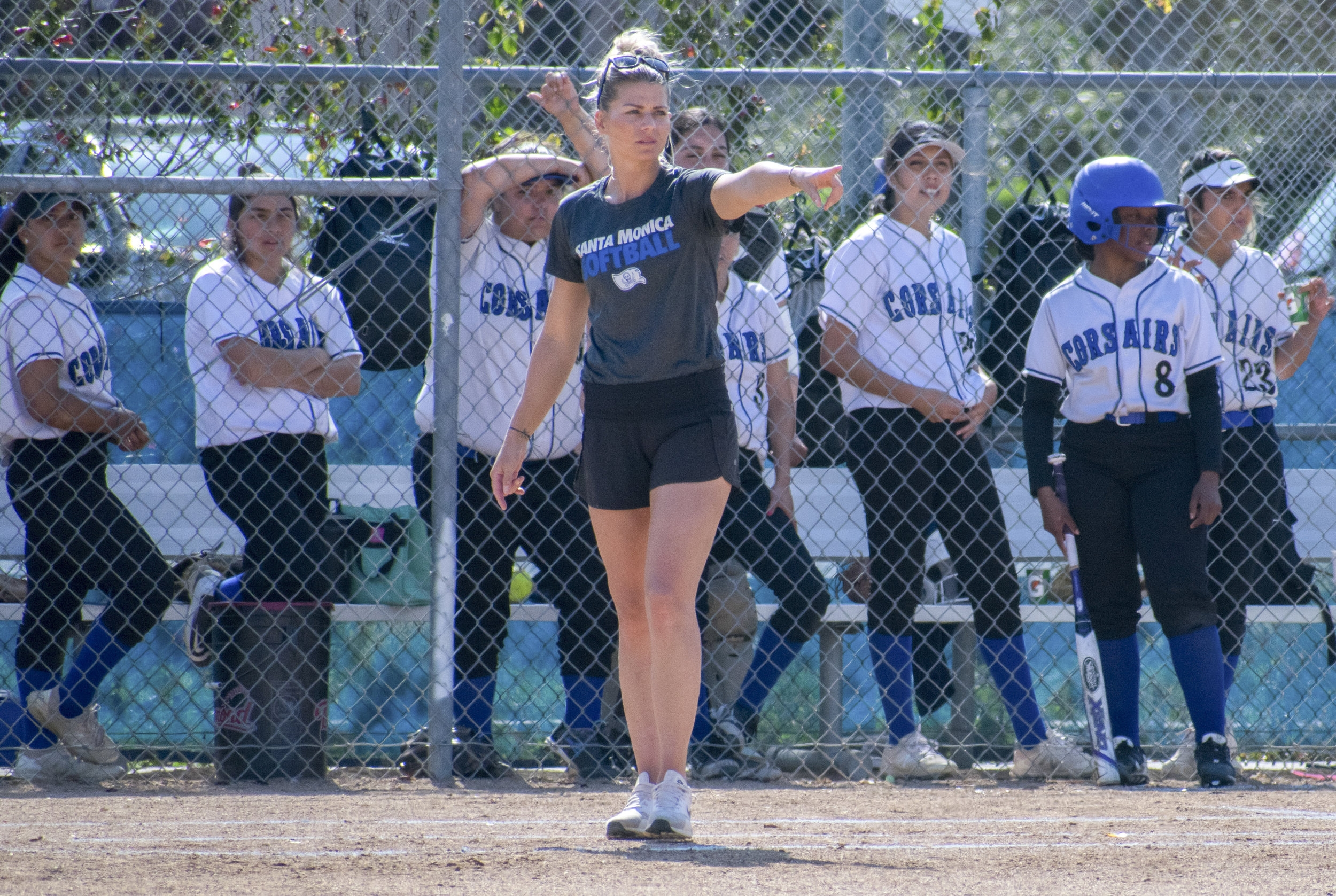 Assistant coach Sam Sheeley gives direction as the Santa Monica Corsairs look on from the dugout during a softball game against the Cuesta College Cougars on Tuesday, April 4 at the John Adams Middle School Field in Santa Monica, California. It was a close 10-inning game, which ended in a 6-5 loss for the Corsairs. (Ethan Lauren/Corsair Photo)
