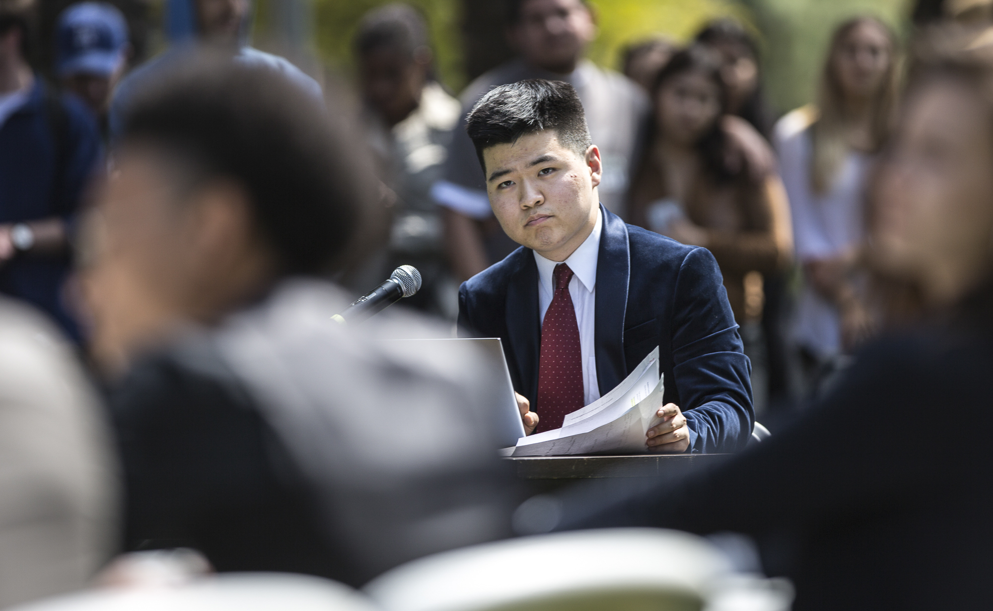 Santa Monica College Corsair Newspaper Editor in Chief Edward Lee reads questions sent in from the audience of students and faculty for Associated Student Board candidates to answer during the A.S election debate on the quad of the Santa Monica College main campus in Santa Monica California, on Tuesday, April 3 2018. The SMC Corsair Newspaper hosted the forum for A.S debate that took place. (Matthew Martin/Corsair Photo)