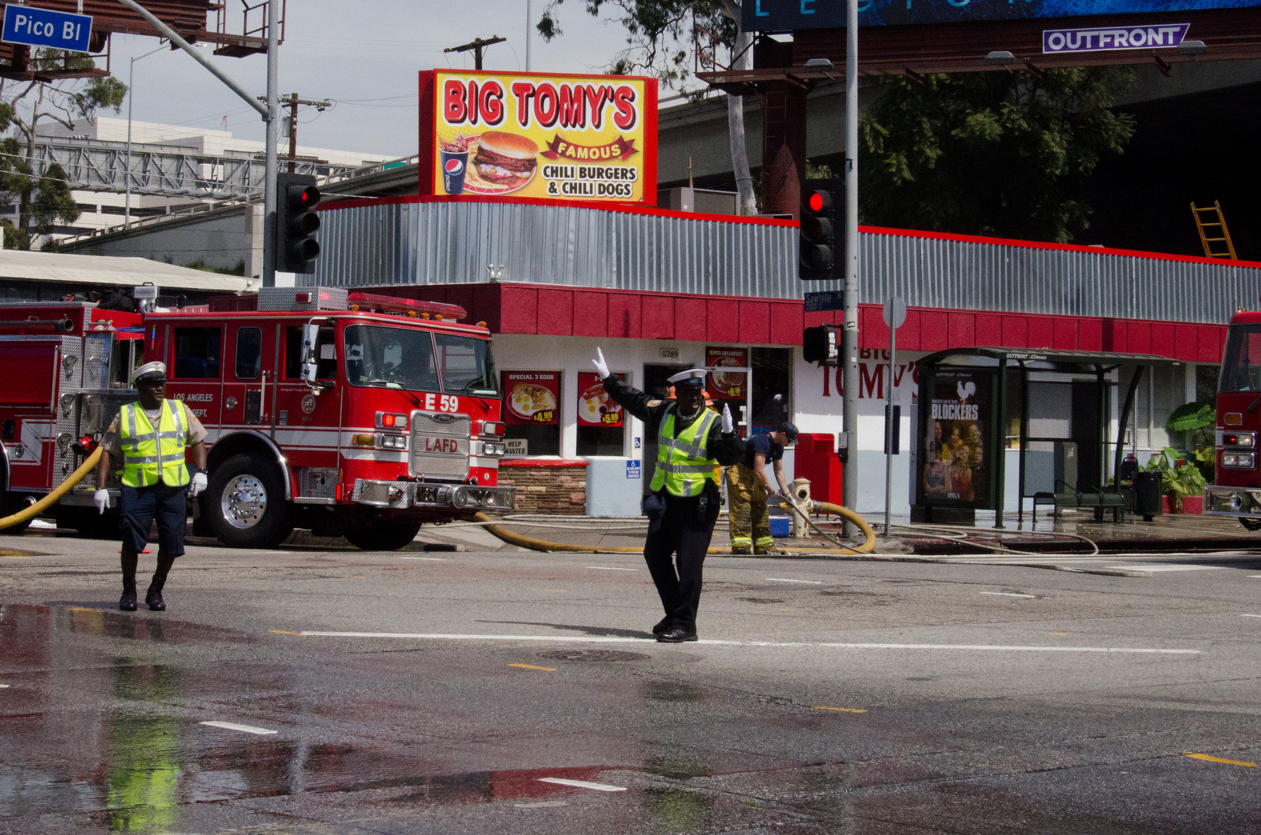Traffic officers control the area around Big Tomy's on the corner of Sawtelle and Pico in Santa Monica, California shortly after a fire which started behind the grill was extinguished by firefighters from LAFD Station 37 on April 6th, 2018. (Reed Curtis/Corsair Photo)