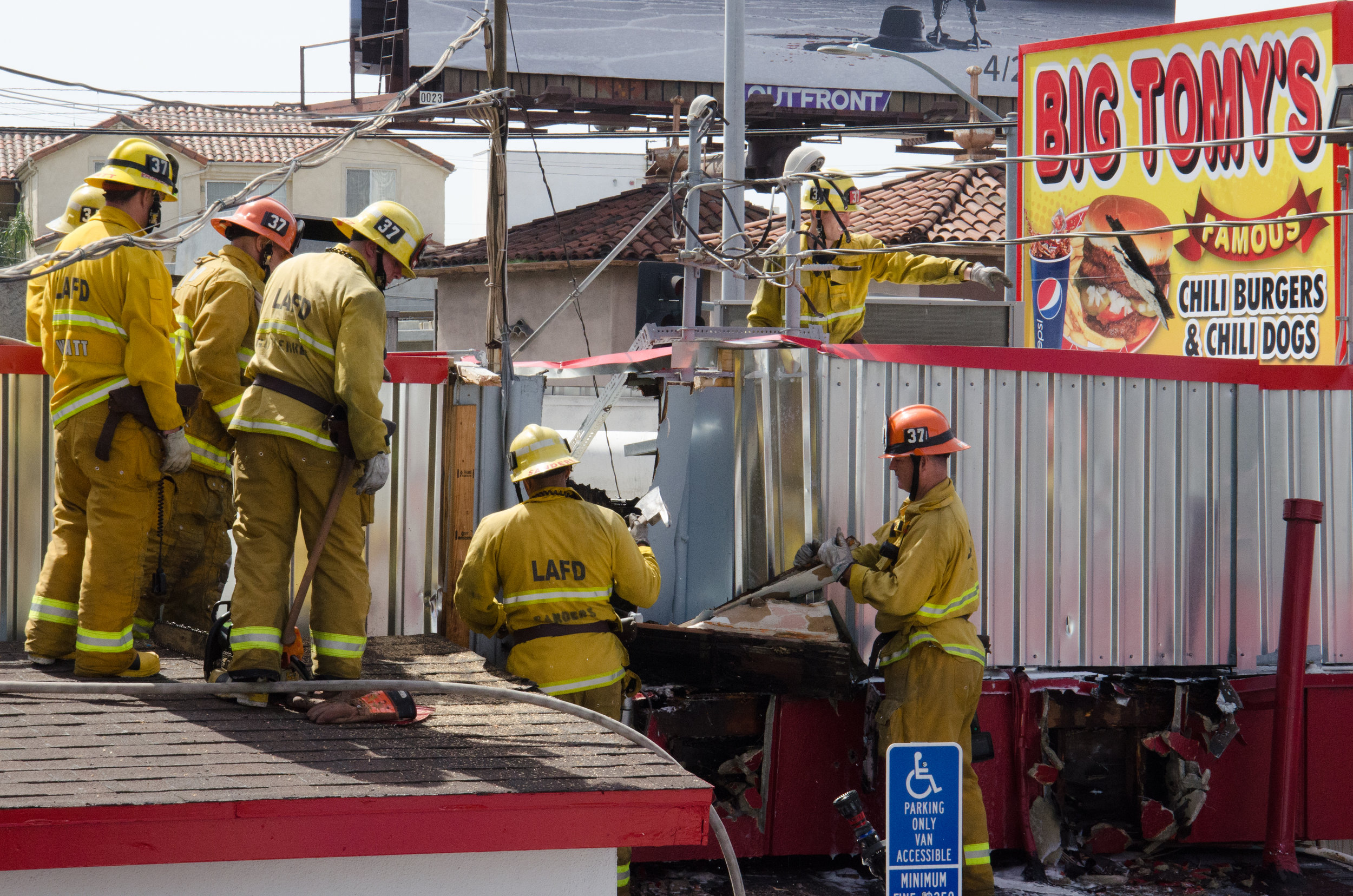 LAFD Firefighters from Station 37 demolish part of the roof of Big Tomy's Hamburgers at the corner of Pico and Sawtelle in Santa Monica, California in order to fight a fire burning within the restaurant's wall. April 6th, 2018 (Reed Curtis/Corsair Photo)