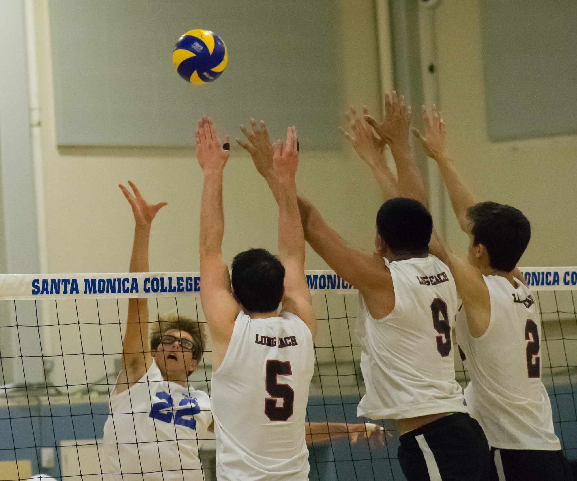 Santa Monica Corsairs sophomore and outside hitter Stanton Smith (#22) attempts to defend against the Long Beach City College Vikings during their final home game of the season on Wednesday, April 12, 2018 in the Santa Monica College gym at Santa Monica, California. The game ended in a 3-1 loss for the Corsairs, giving them a 7-7 overall rating for the season with one game left. (Ethan Lauren/Corsair Photo)