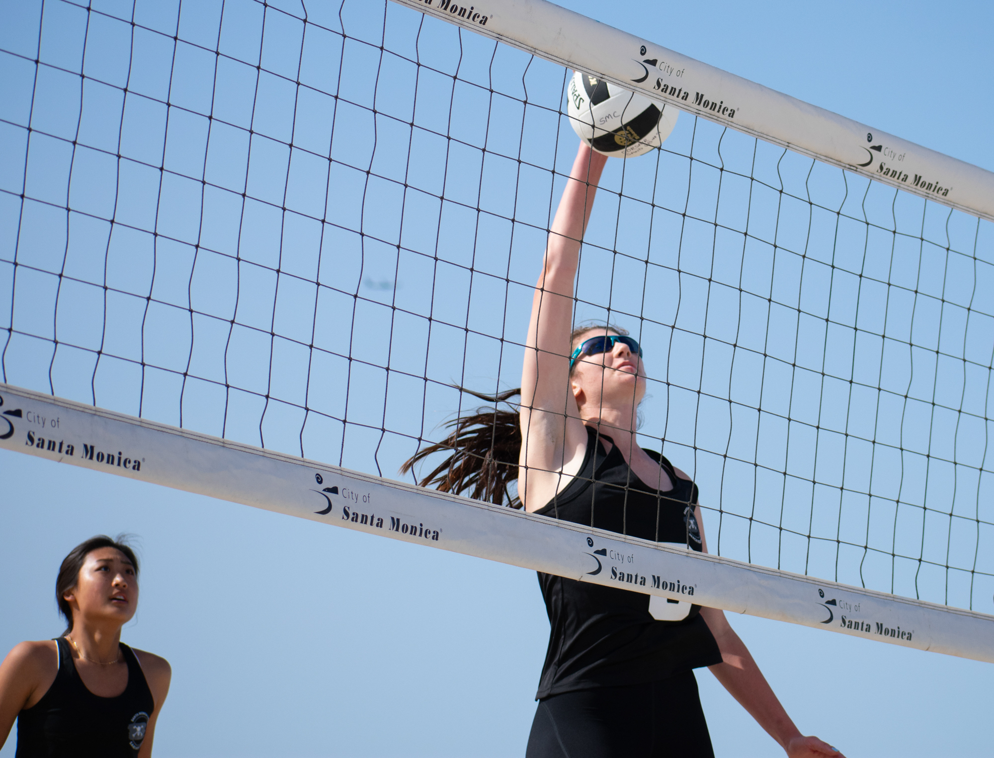 Santa Monica College Corsair Chelsea Bostwick (#3) attempts to spike the ball as partner Megan Yoon (#11) looks on during a conference game of beach volleyball in court one against the Ventura College Pirates at the Santa Monica beach on Friday, April 13, 2018 in Santa Monica, California. It was a 4-1 loss for the Corsairs, bringing their total to 2-11 for the season and it was this court brought the only win. (Ethan Lauren/Corsair Photo)
