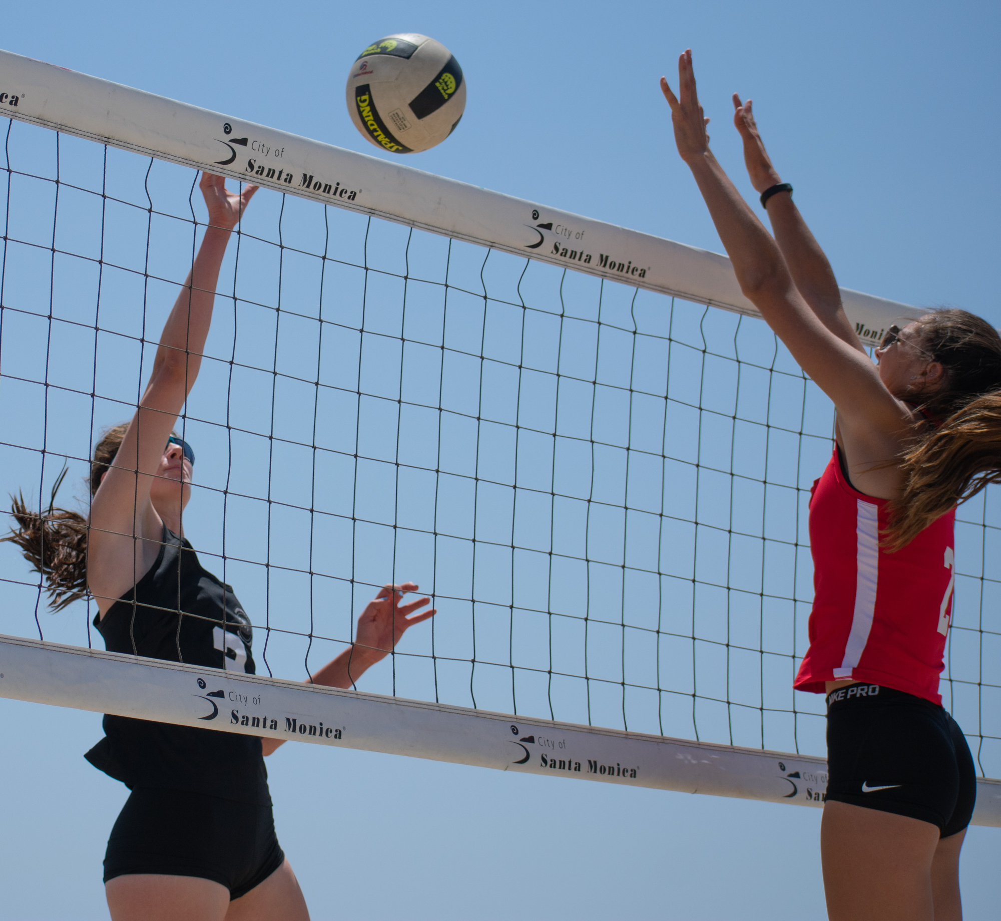 Santa Monica College Corsair Chelsea Bostwick (#13) hits the ball over the net during a conference game of beach volleyball in court one as the Bakersfield College Knights try to defend at the Santa Monica beach on Friday, April 13, 2018 in Santa Monica, California. It was a 5-0 loss for the Corsairs, bringing their total to 2-12 for the season. (Ethan Lauren/Corsair Photo)