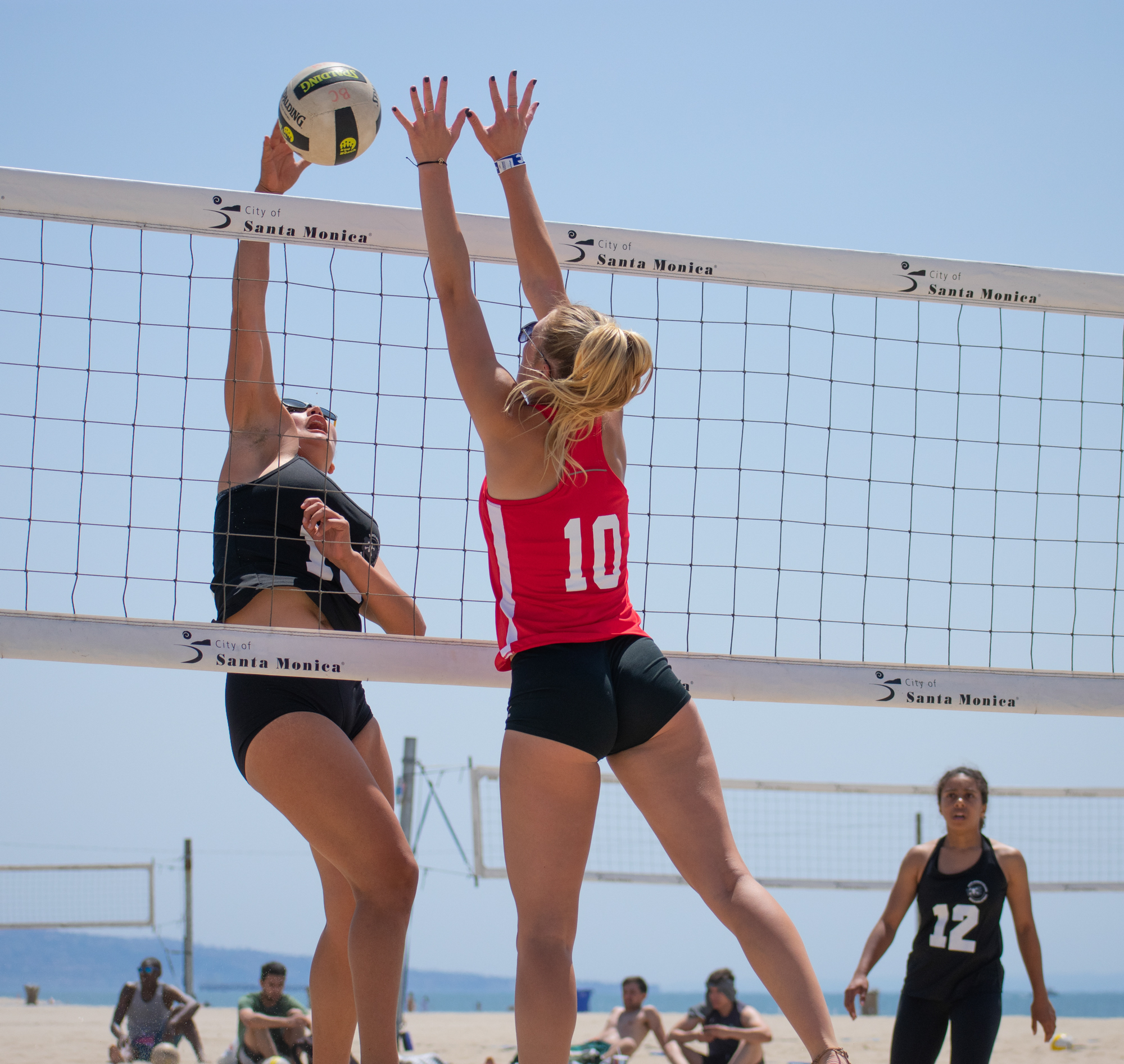 Santa Monica College Corsair Ada Nadzakova (#13) attempts to defend against Bakersfield College Knight Alex Paris (#10) as Corsair Taylor Burks (#12) looks on during a conference game of beach volleyball in court two at the Santa Monica beach on Friday, April 13, 2018 in Santa Monica, California. It was a 5-0 loss for the Corsairs, bringing their total to 2-12 for the season. (Ethan Lauren/Corsair Photo)