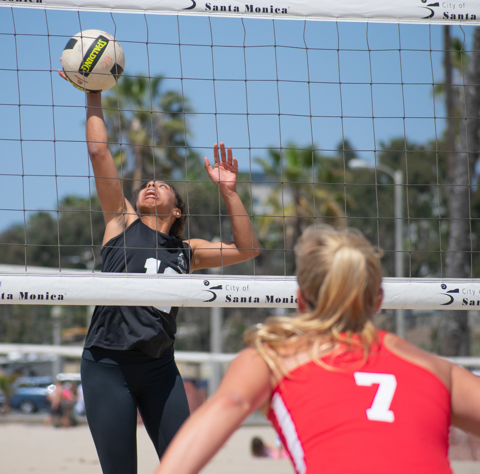 Santa Monica College Corsair Taylor Burks (#12) tries to defend against Bakersfield College Knight Haley Sanchez (#7) during a conference game of beach volleyball in court two at the Santa Monica beach on Friday, April 13, 2018 in Santa Monica, California. It was a 5-0 loss for the Corsairs, bringing their total to 2-12 for the season. (Ethan Lauren/Corsair Photo)