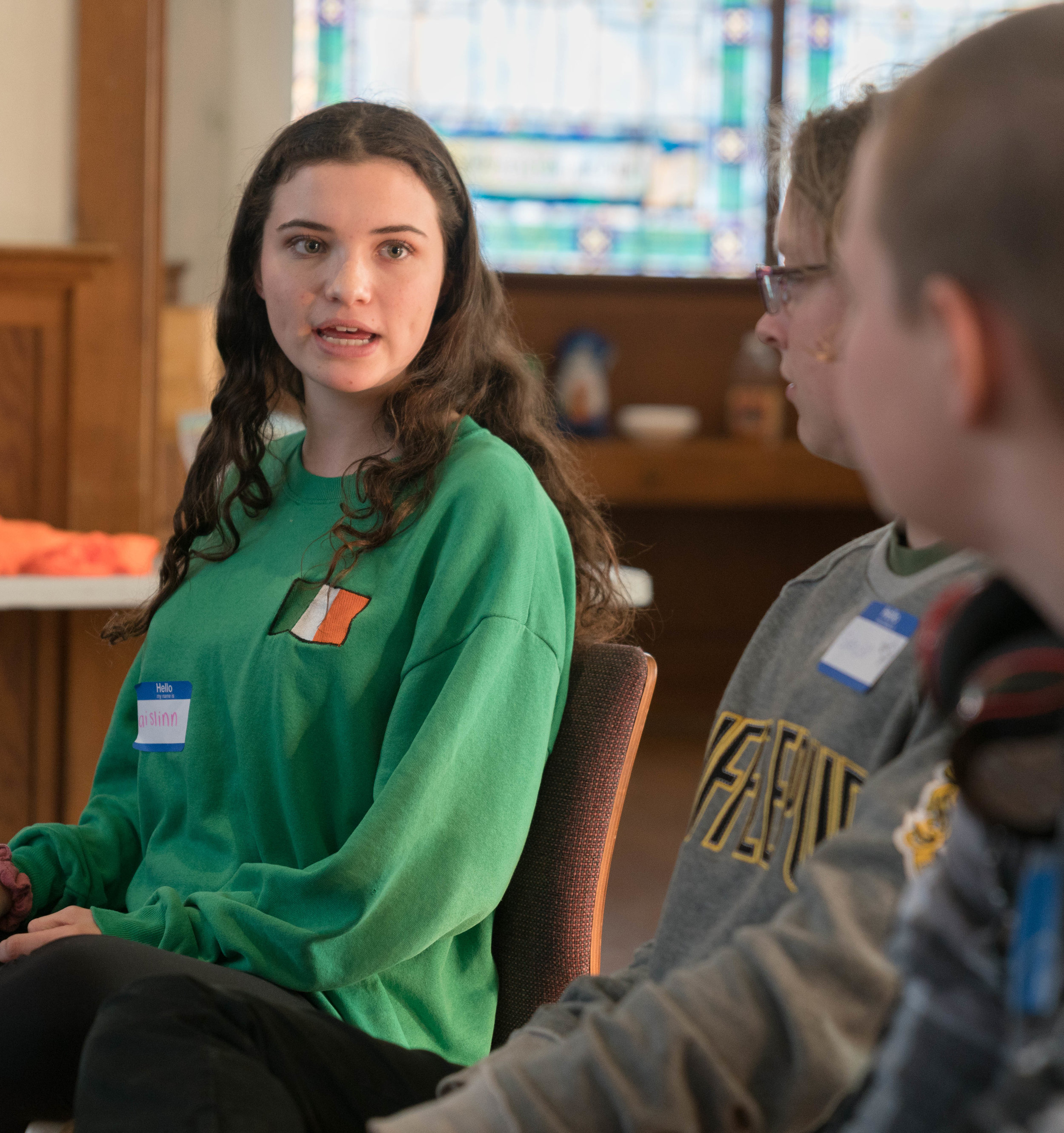Aislinn Russell (left), a sophomore at Crossroads School for Arts & Sciences, speaks with Santa Monica High School students, Spencer Newman (center) and Roger Gawne (right), at a meeting in Santa Monica, California on Tuesday, April 17, 2018. (Helena Sung/Corsair Staff)