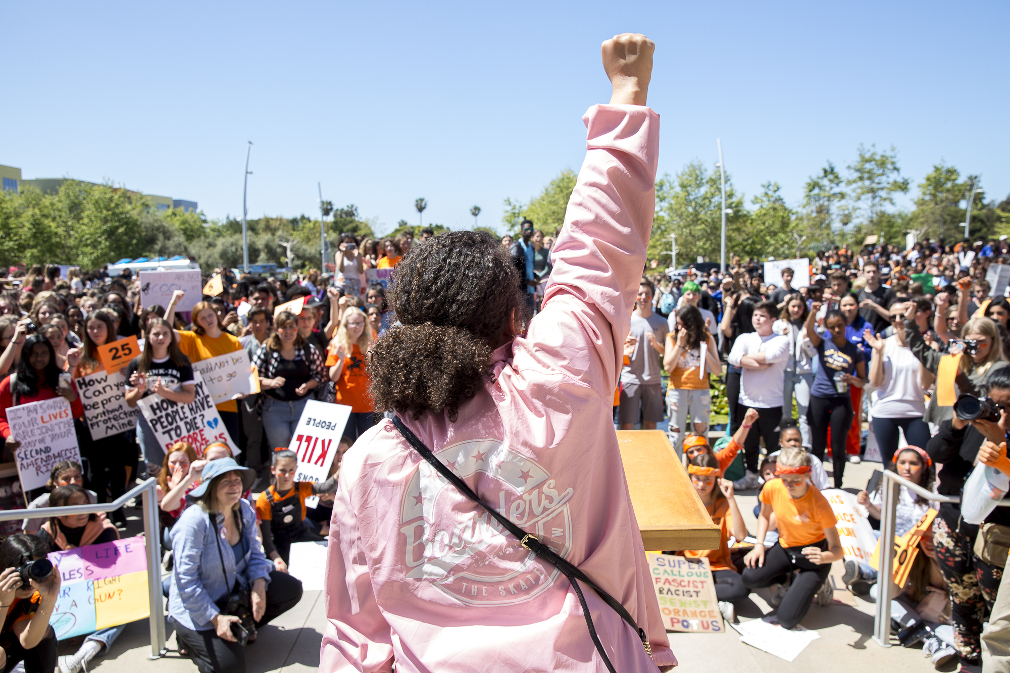 """Flora Chavez (21), one of the key speakers during the student walkout that converged at Santa Monica City Hall sings a song she wrote entitled, """"Peace Love Unity"""" to those in attendance in Santa Monica California, on Friday, April 20 2018. Several hundred students from area high schools and middle schools converged on Santa Monica City Hall in protest against all forms of gun violence, marking also the 19th anniversary of the Columbine High School massacre. (Matthew Martin/Corsair Photo)"""