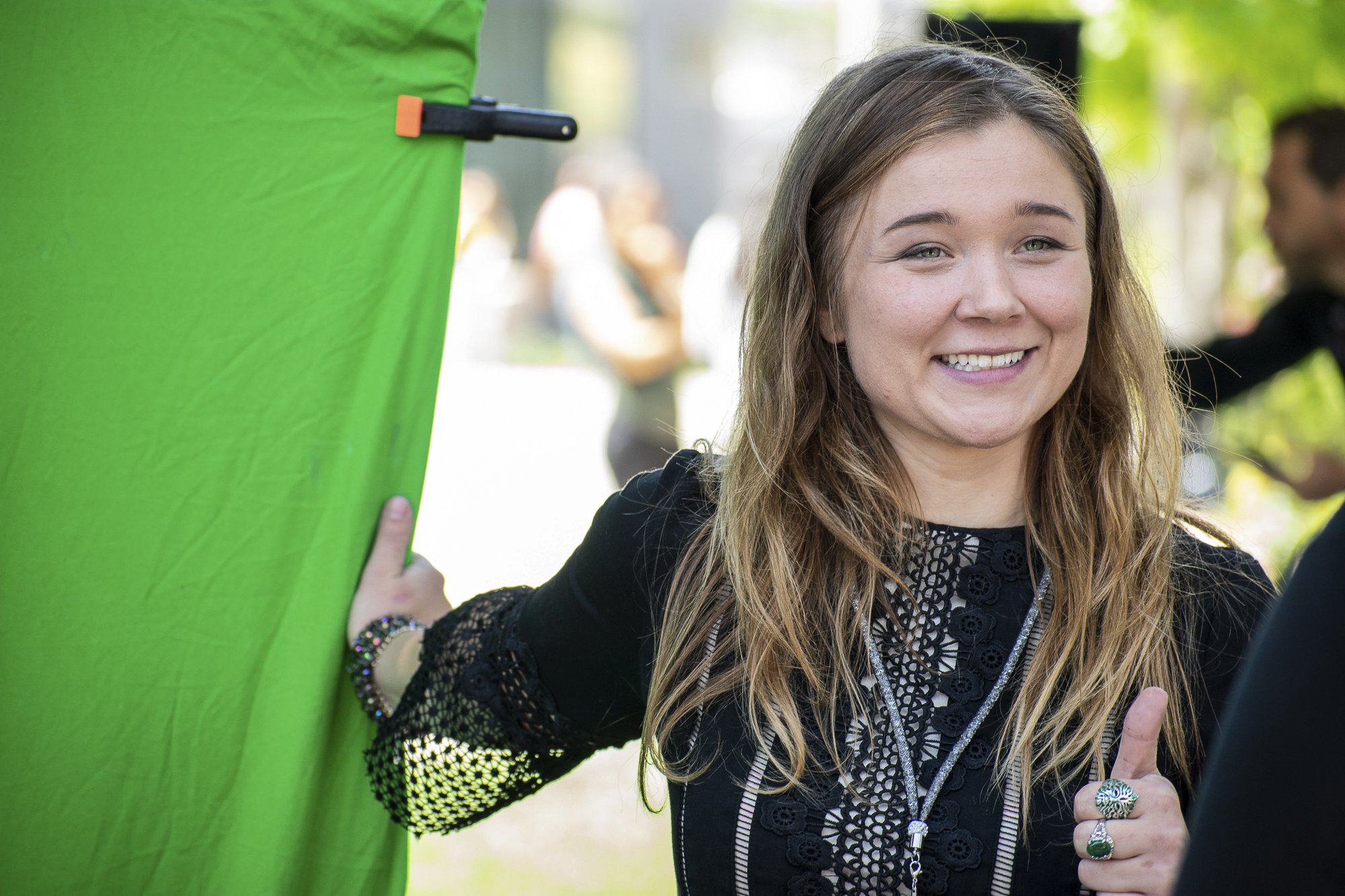 On the quad at Santa Monica College, Katharine Nilsen stands next to a green screen for Urban Mediamakers West during Club Row on Thursday, April 26, 2018 in Santa Monica, California. With over 60 clubs in attendance, the day is meant to encourage clubs to showcase what they've been doing over the semester for students. (Ethan Lauren/Corsair Photo)